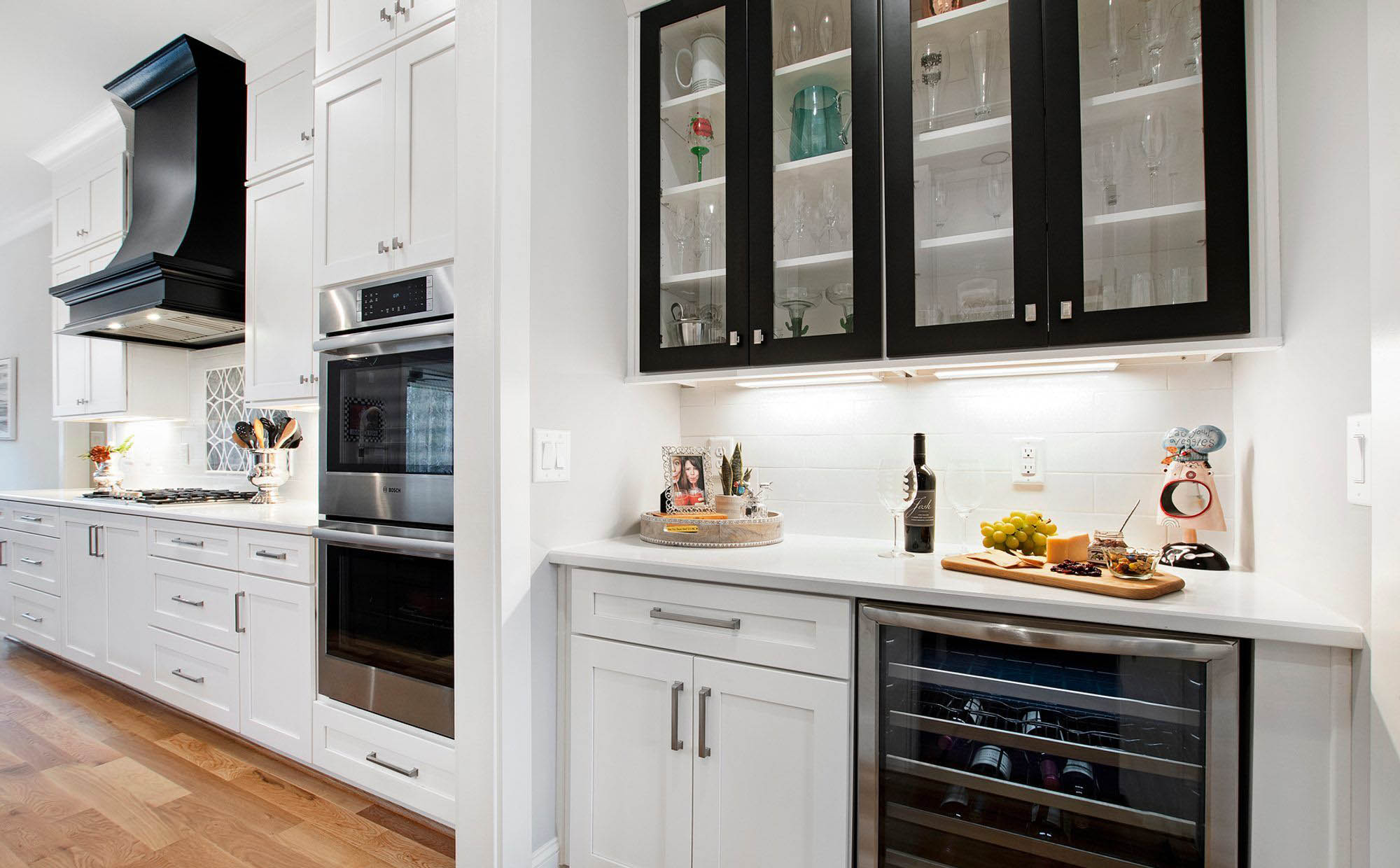 White and black kitchen color scheme with white quartz counters. A mix of white and black cabinets with brushed metal hardware. quartz vs granite.