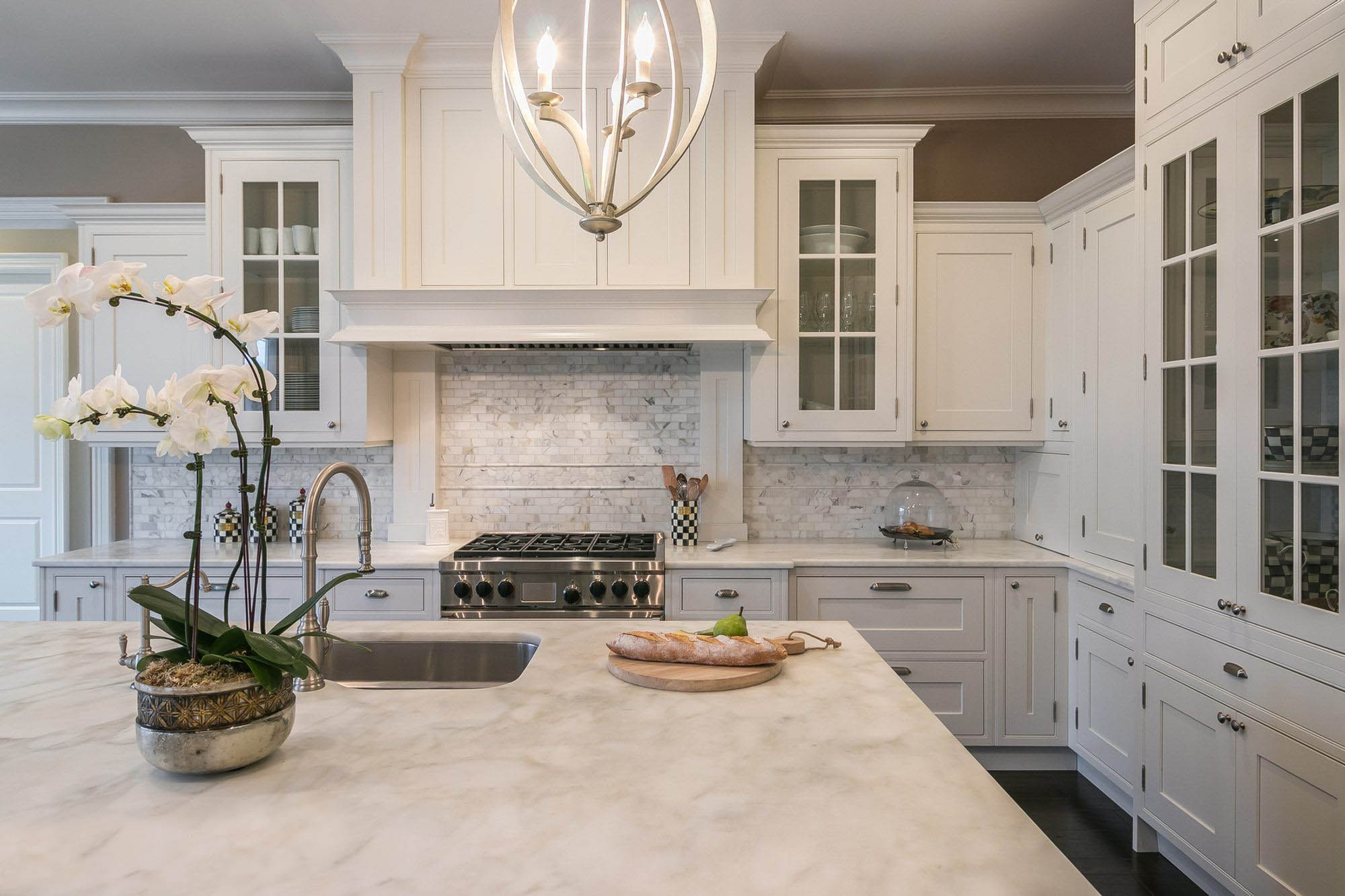 White marble quartz with white cabinets and real marble backsplash. Dark hardwood floors with tan walls. quartz vs granite.