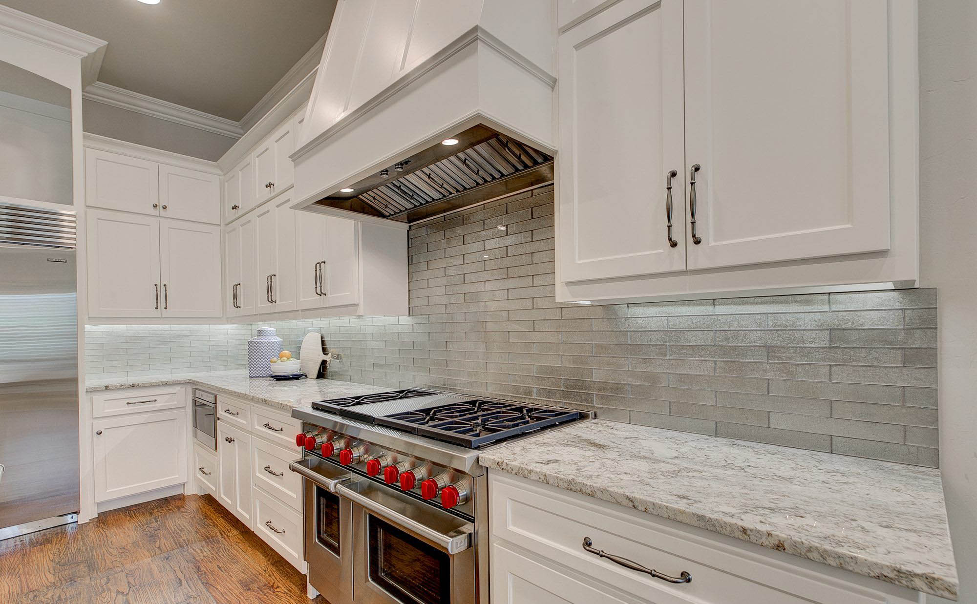 White granite countertops with white cabinets and gray tile backsplash. Wolf range with dual ovens. quartz vs granite.