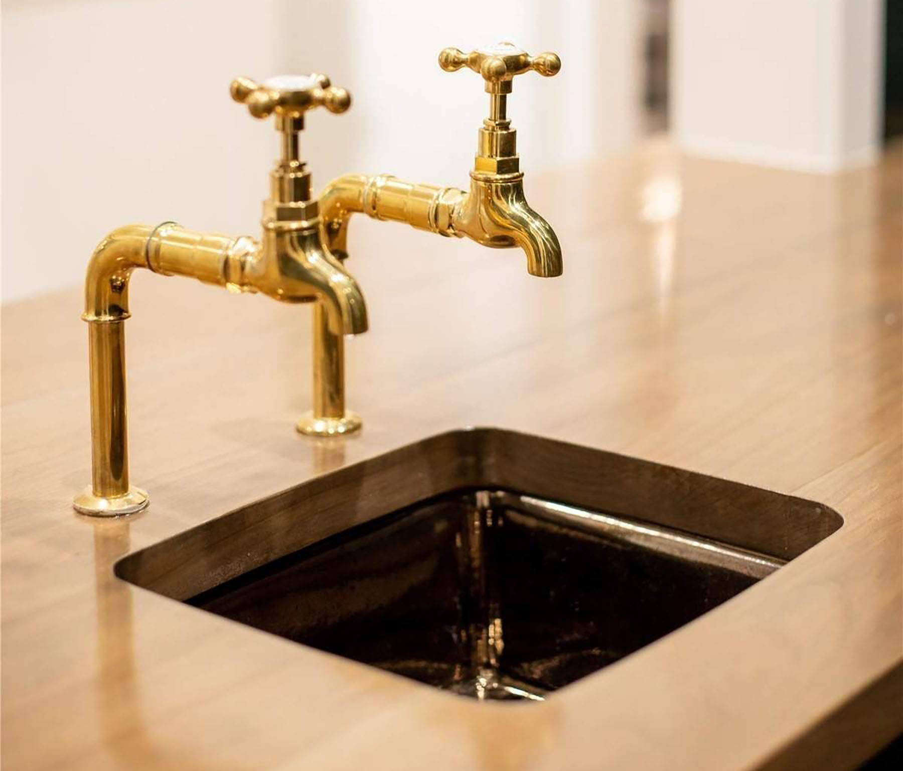 Closeup view of a small copper kitchen sink with old fashioned gold faucets.