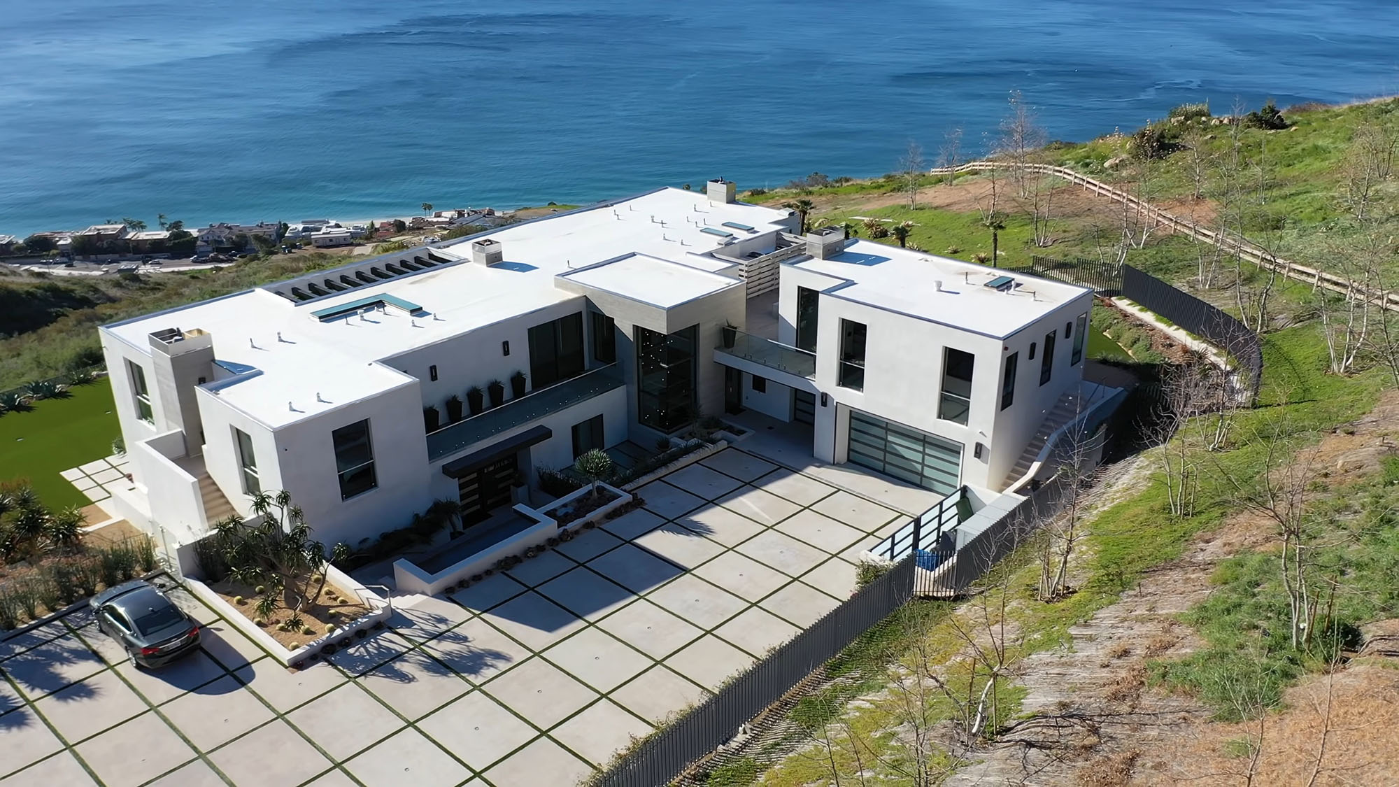Modern oceanfront custom hoe with flat roof and parapet walls. Huge driveway made with concrete grass squares.