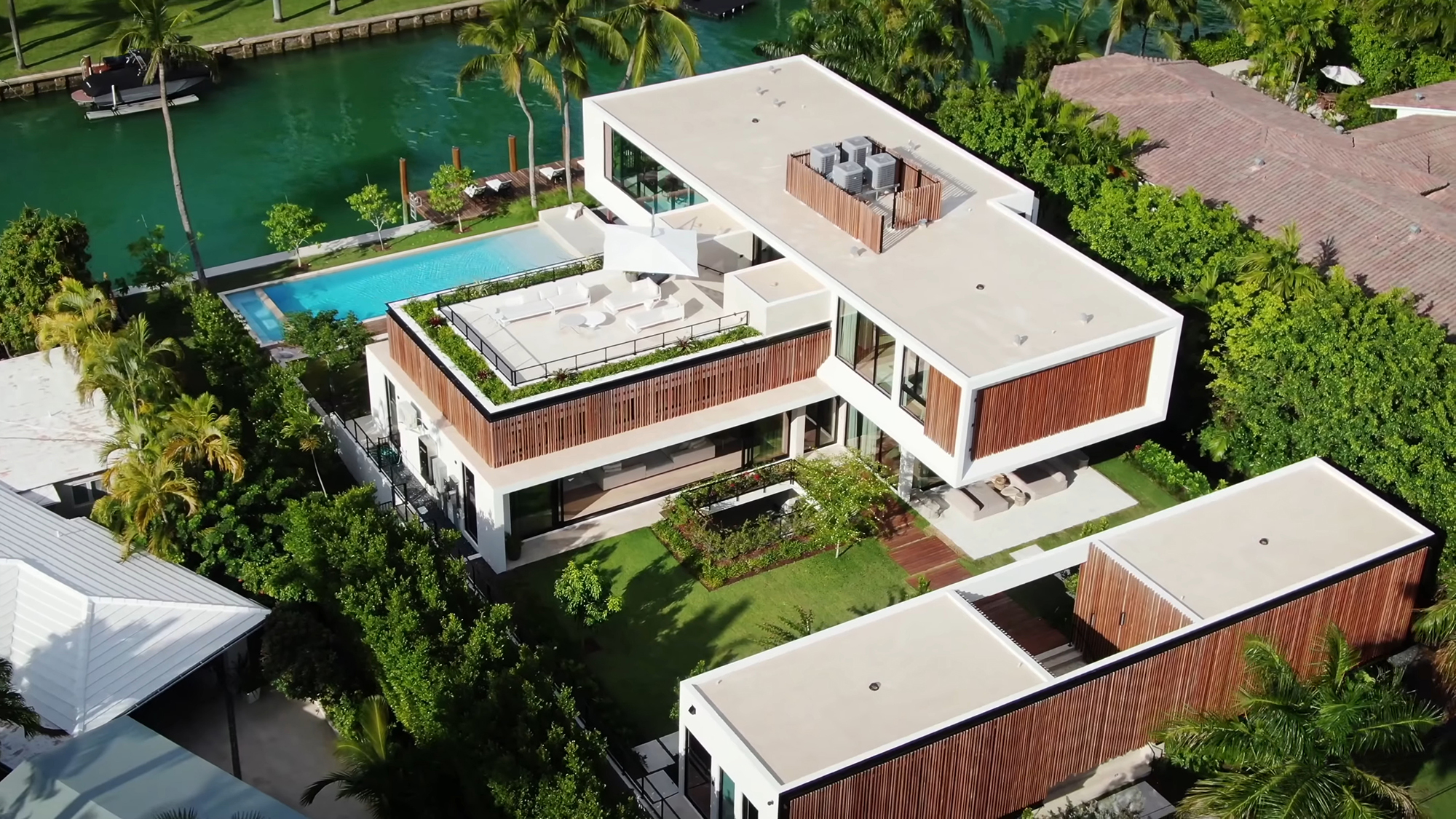 Ariel view of this fantastic contemporary home on a canal in Florida with flat roof and rooftop deck with planters.