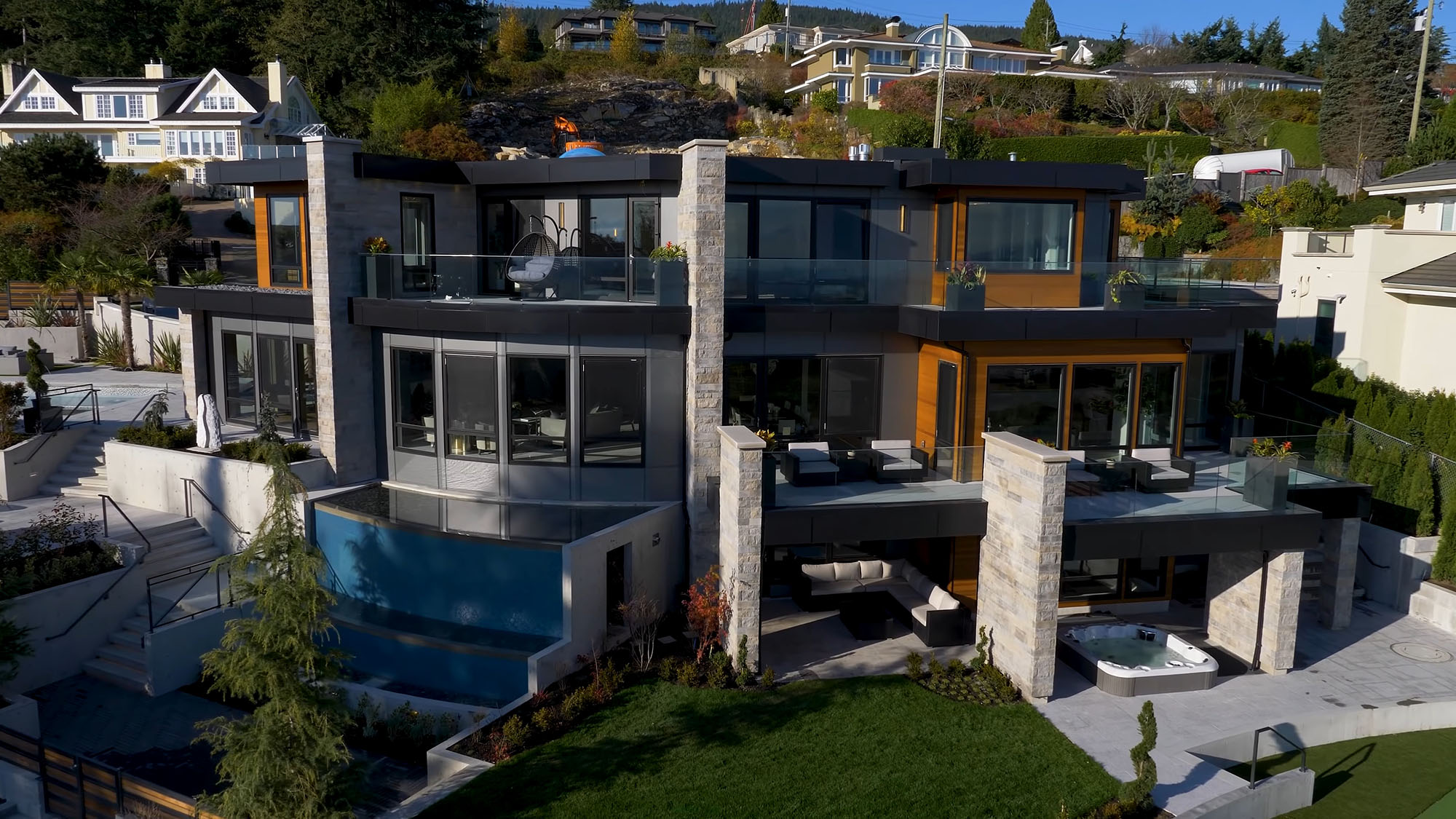 Ultra modern three story house with a flat roof and tons of outdoor living spaces.