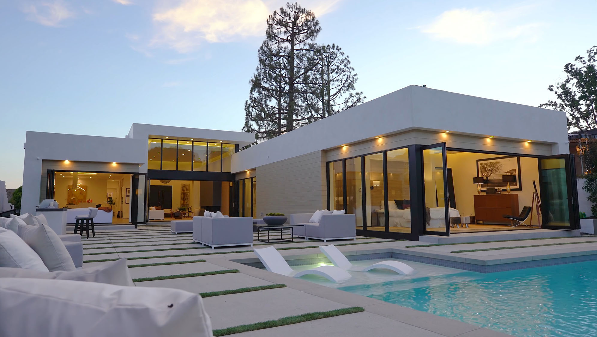 Beautiful contemporary style home with a mix of white and tan stucco, black frame windows and a flat roof.