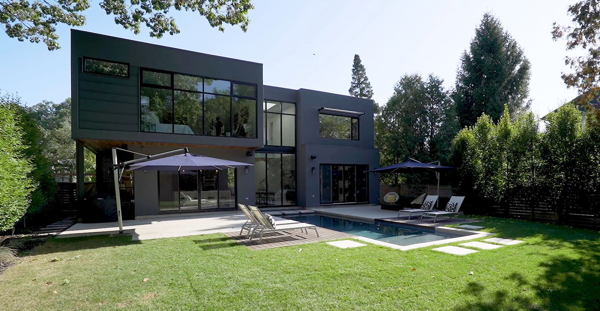 Modern gray house with black frame floor to ceiling windows and a flat roof.