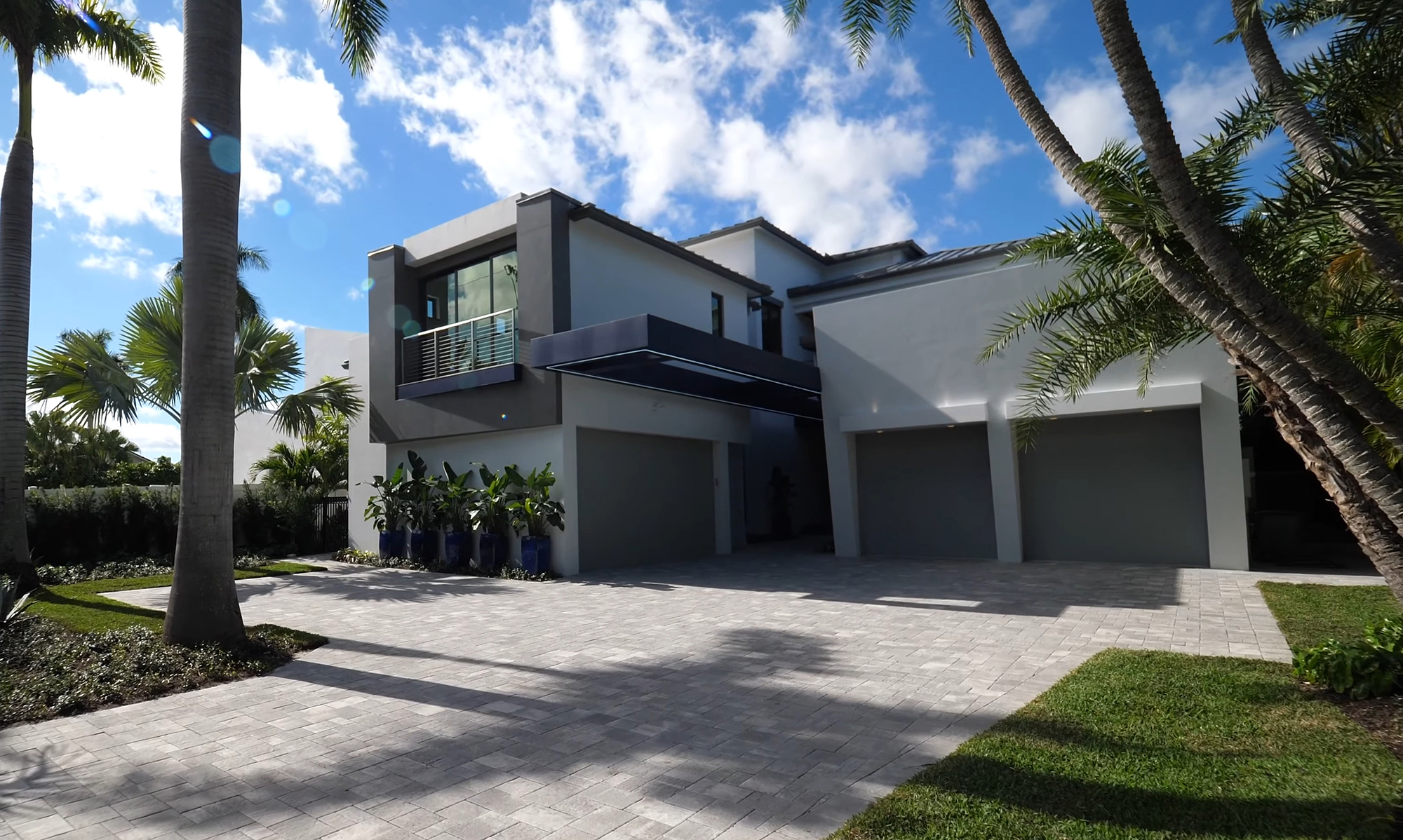 All gray custom home with a modern style and flat roof. Gray paver driveway.
