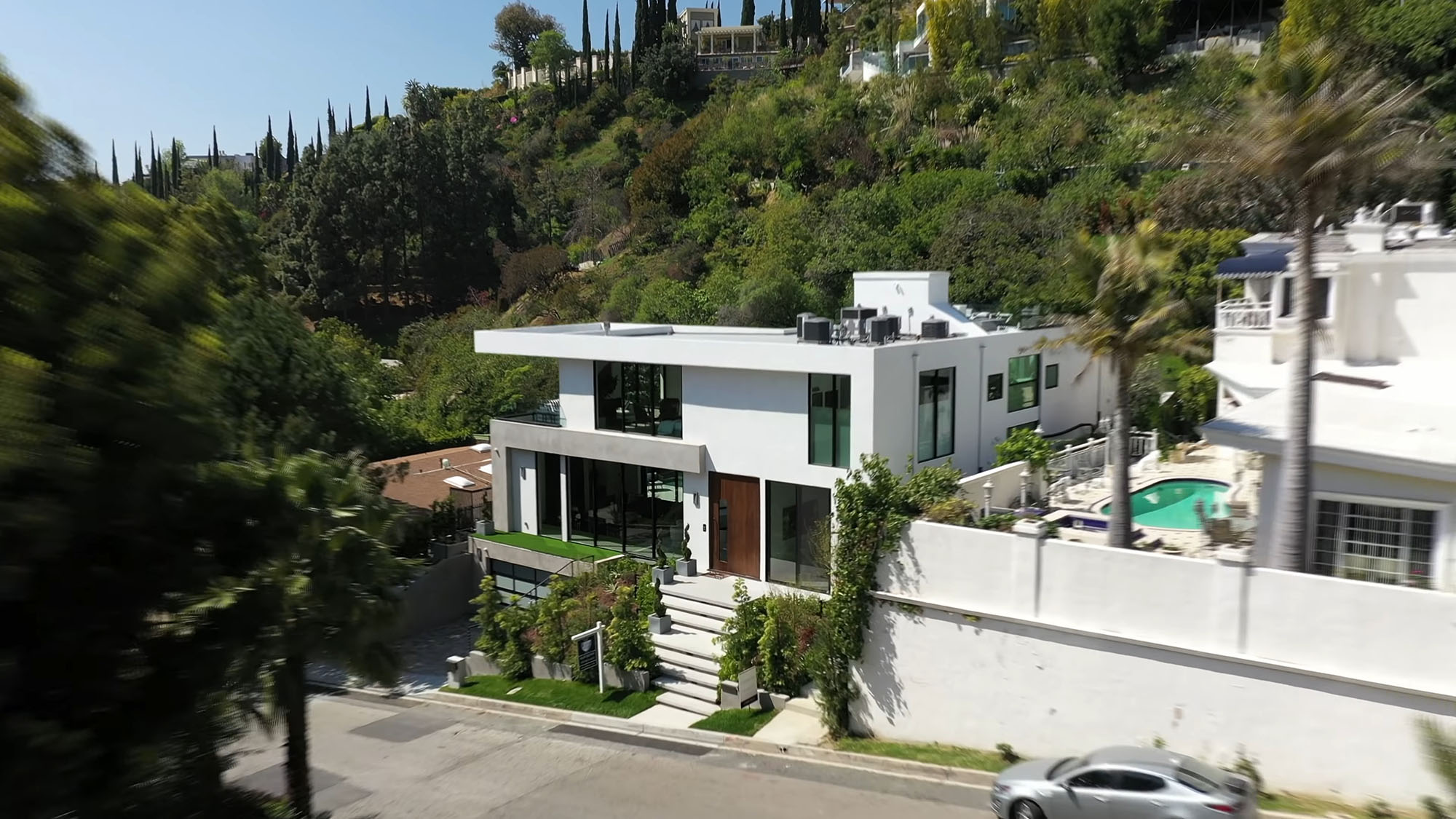 Beautiful white stucco modern home in the California Hills with a flat roof design.
