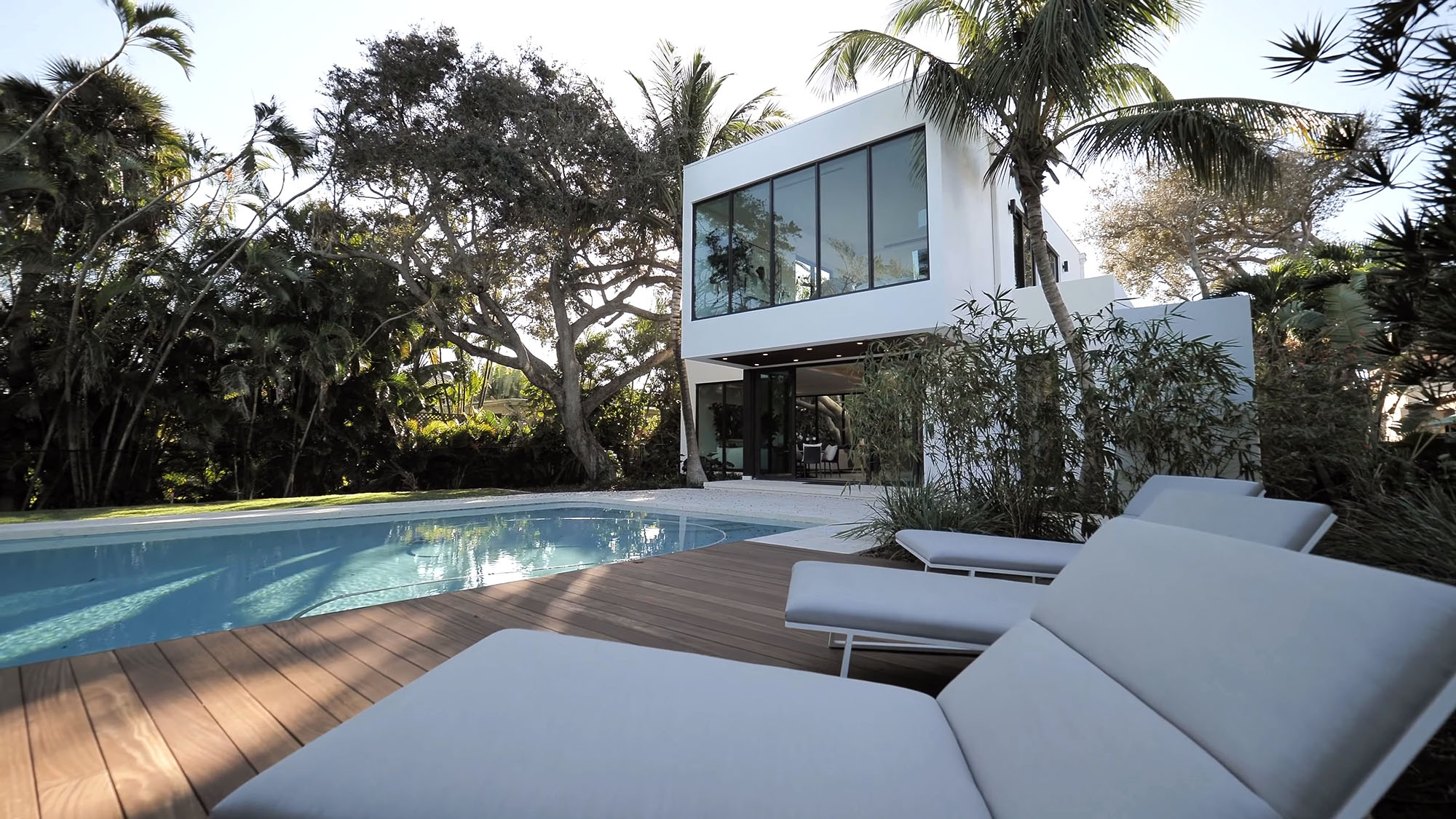 White stucco flat roof home with huge windows overlooking the in ground pool and Ipe deck.