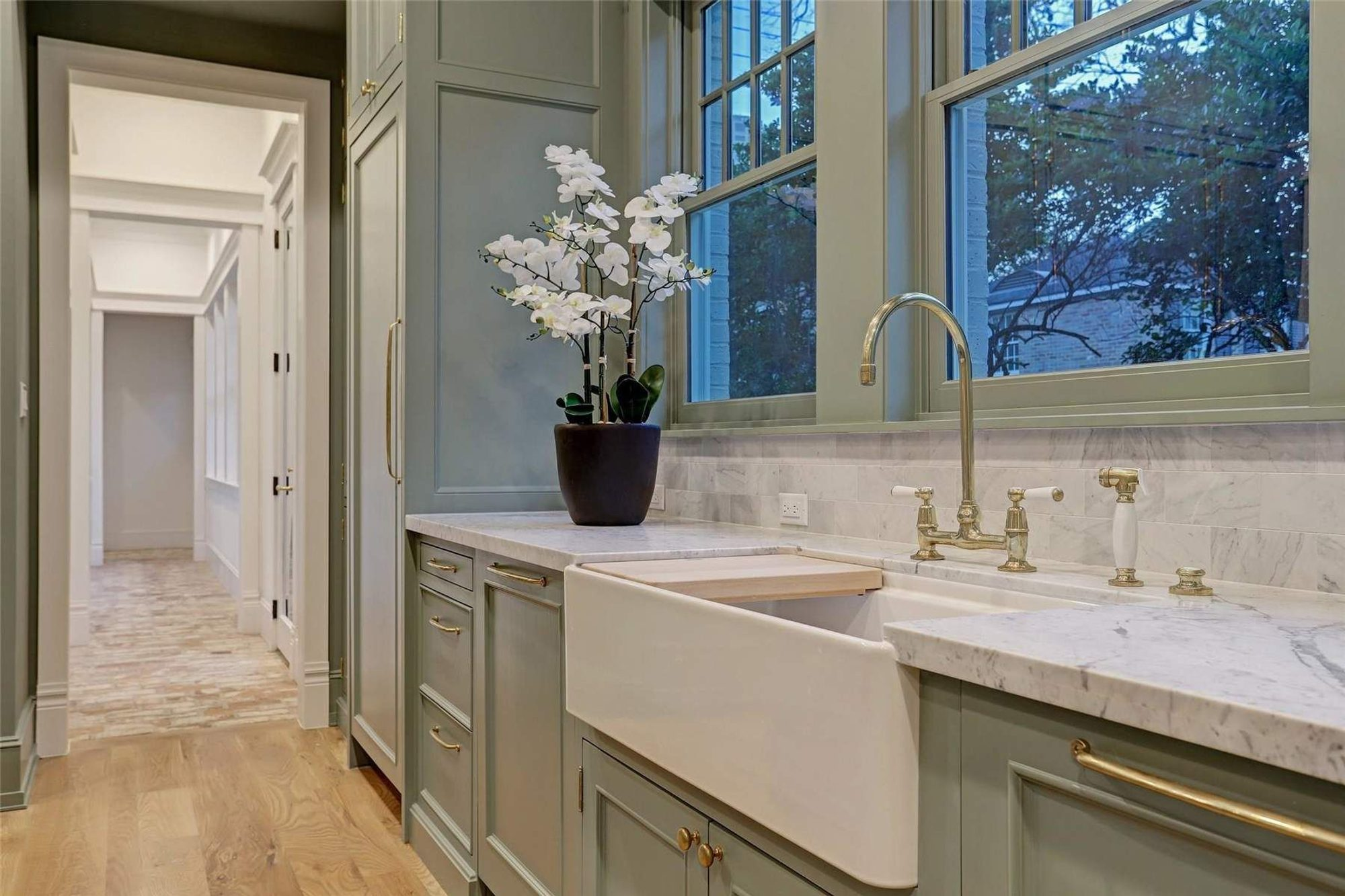 Large farmhouse style single basin white enamel kitchen sink with exposed apron.