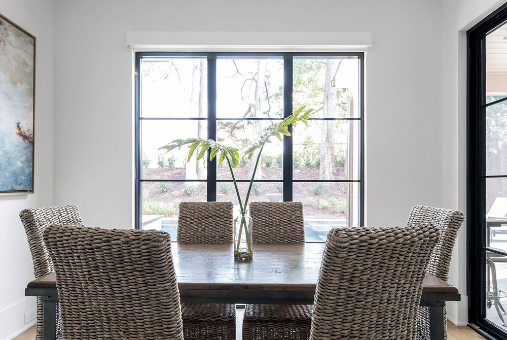 transitional dining room design with black frame windows and no trim
