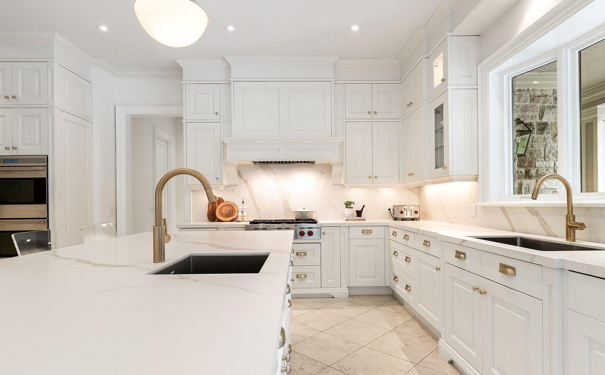 Black stone composite sinks with white quartz countertops.