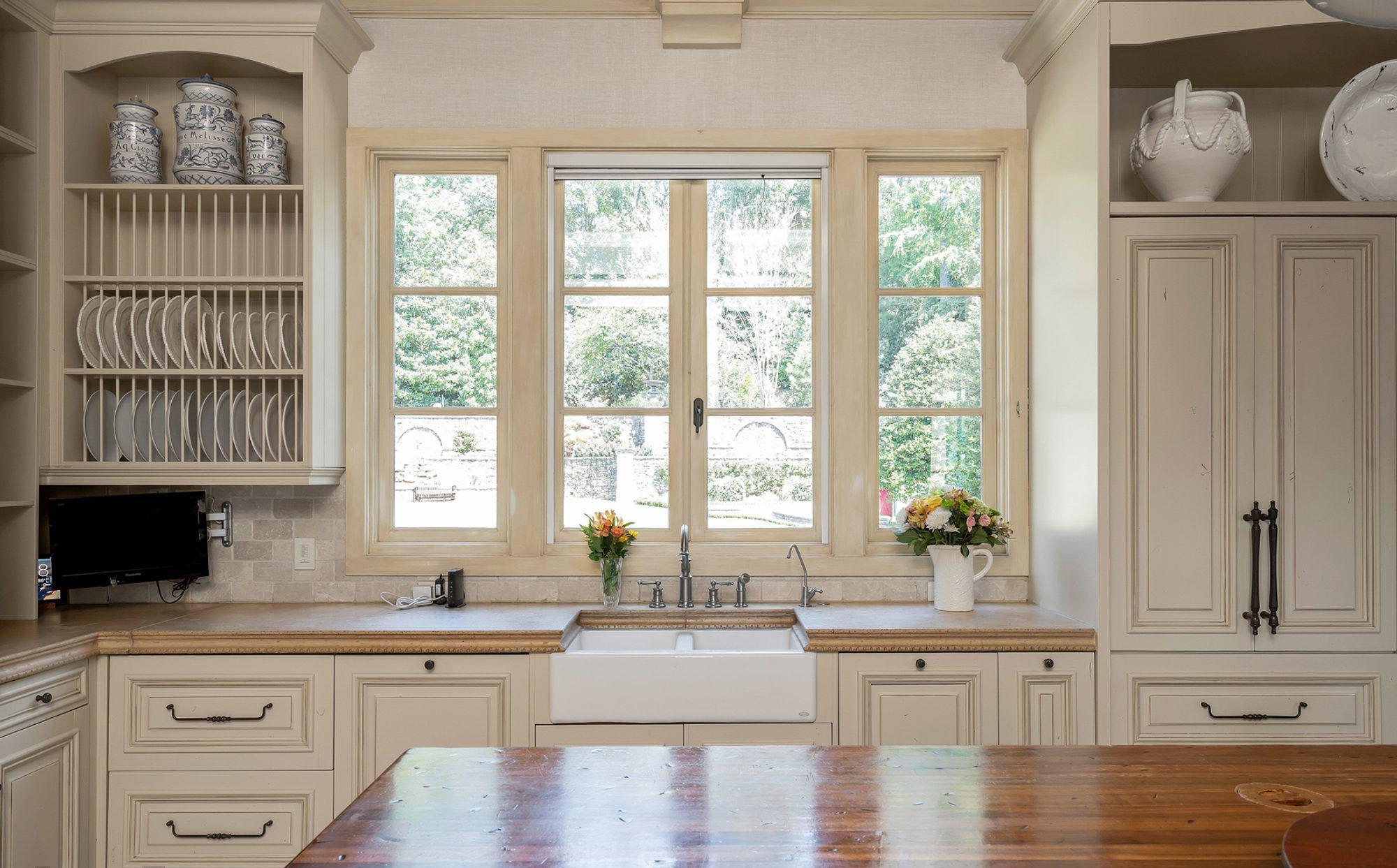 White enamel farmhouse styles kitchen sink with exposed apron.