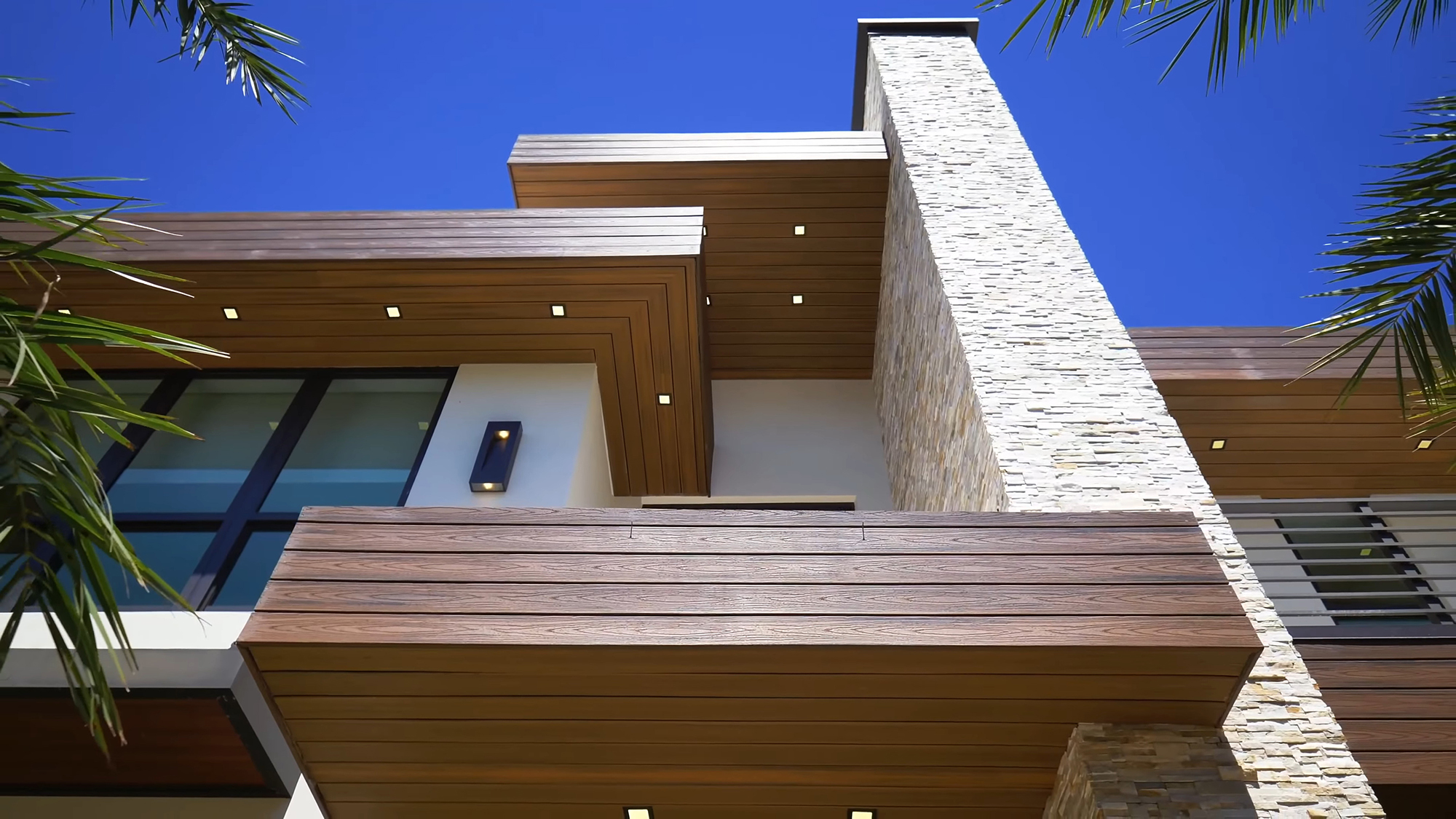 Ground level view of a flat roof house with Trex composite decking used as siding and soffits with square recessed lighting.