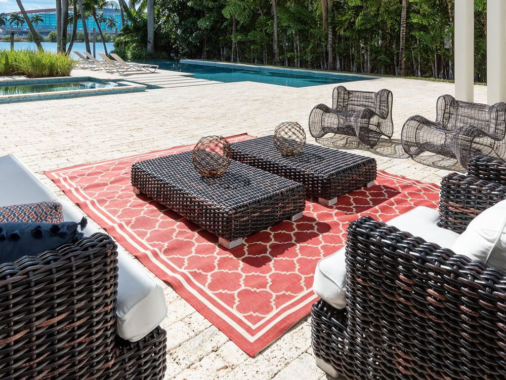 red oatterned modern outdoor area rug surrounded by wicker chairs with white cushions