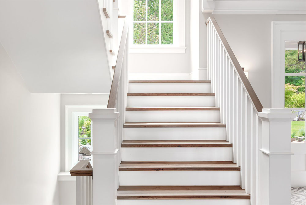 set of beautiful white stairs with light wood steps and hand rail