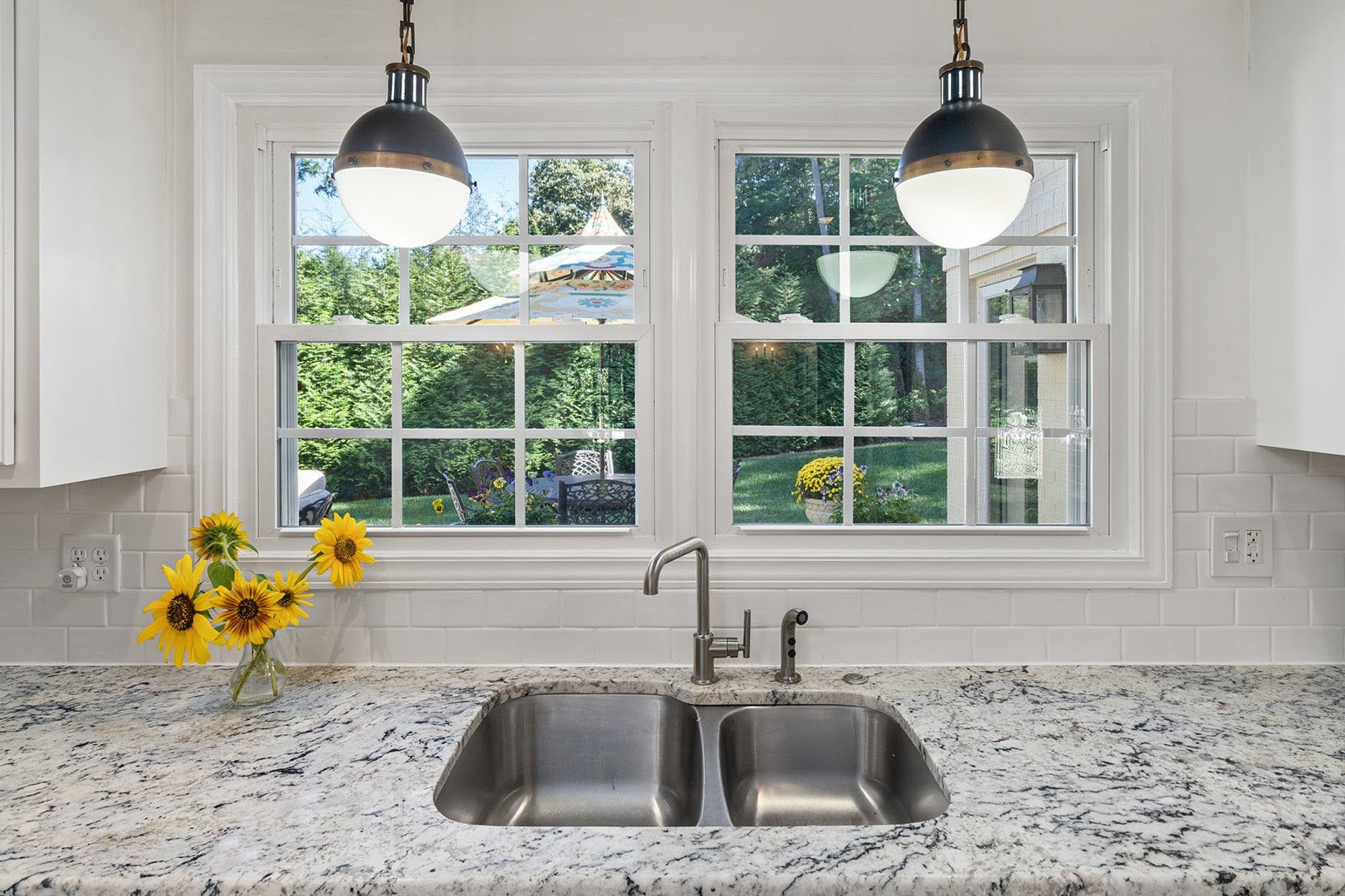 Double basin stainless steel kitchen sink with granite countertops.