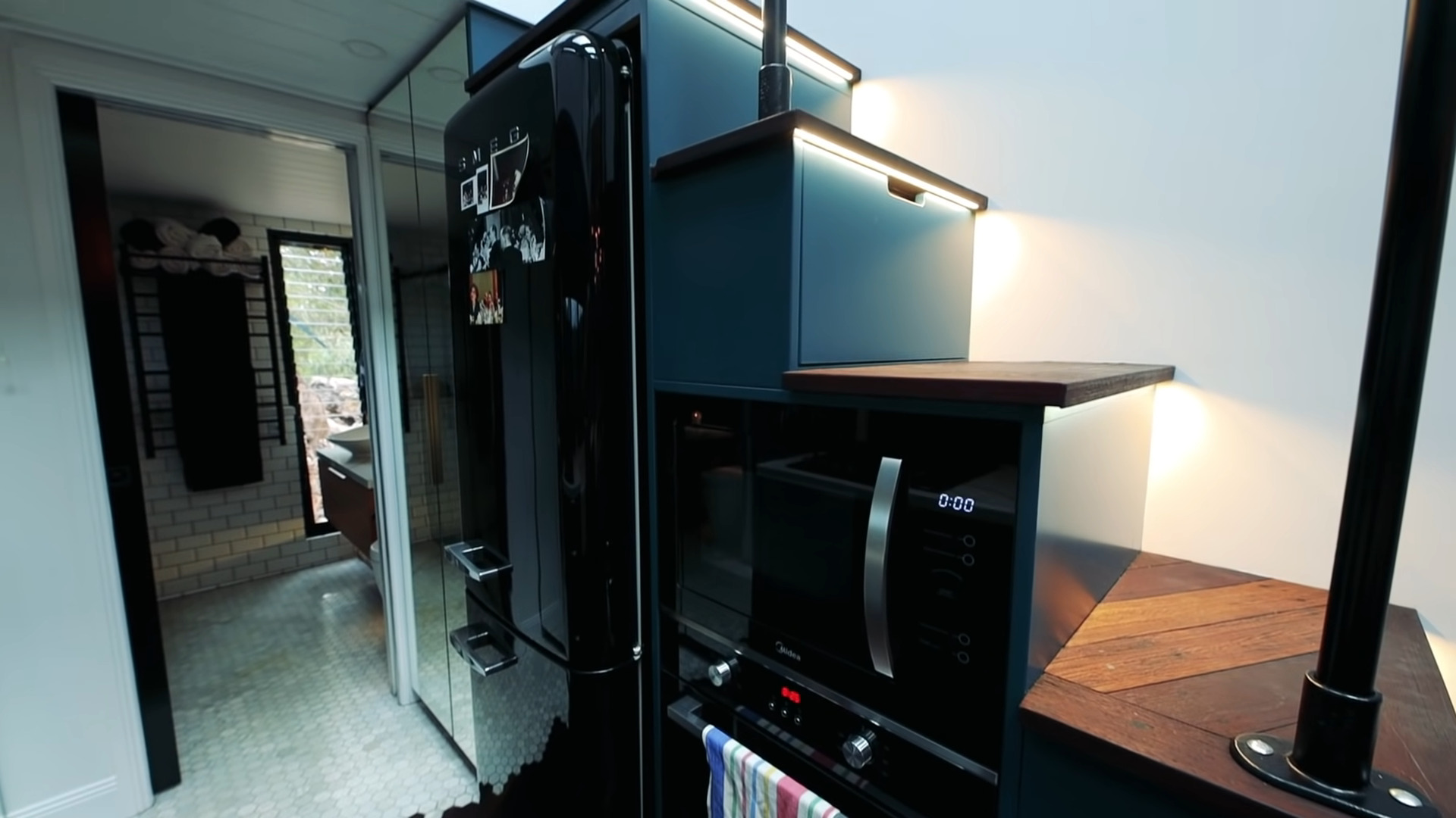 Tiny house bathroom view from the kitchen with sliding black pocket door