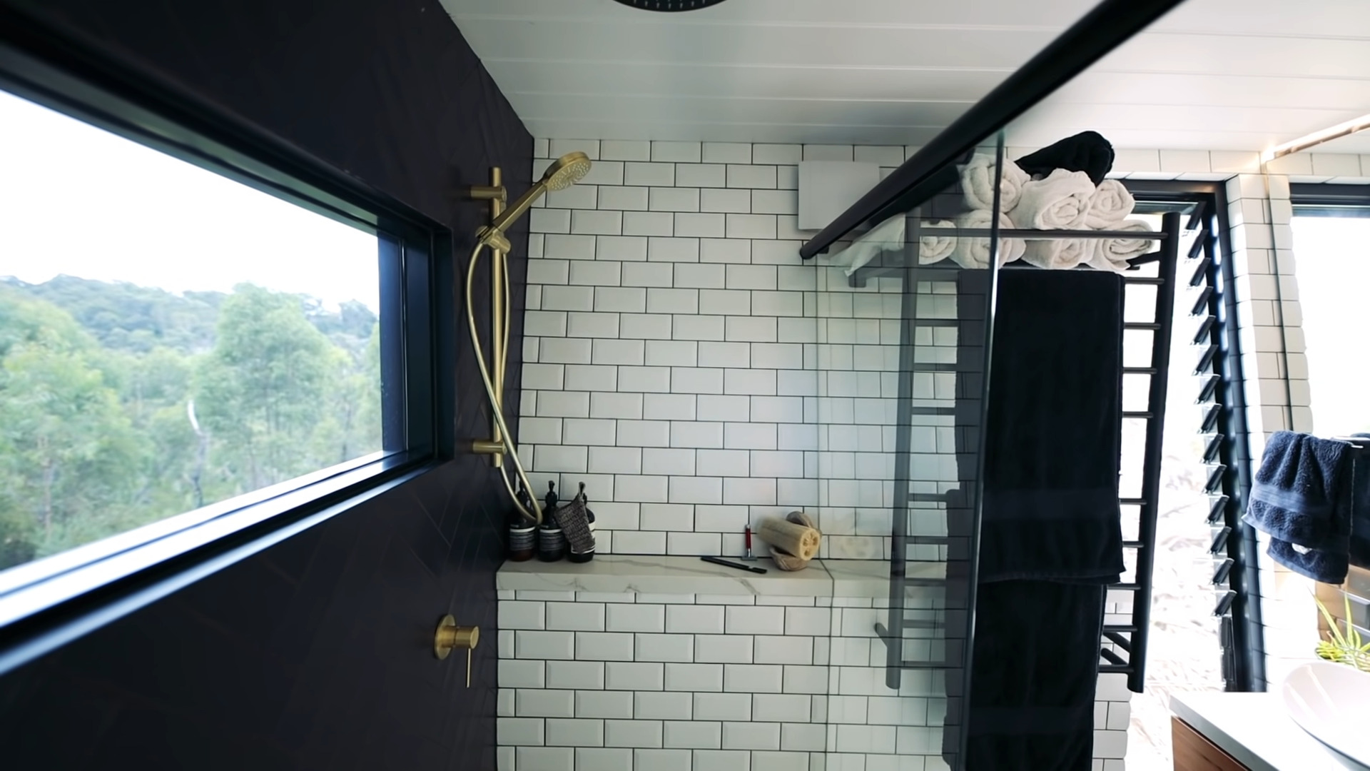tiny house bathroom shower including white subway wall tiles and gold fixtures large window