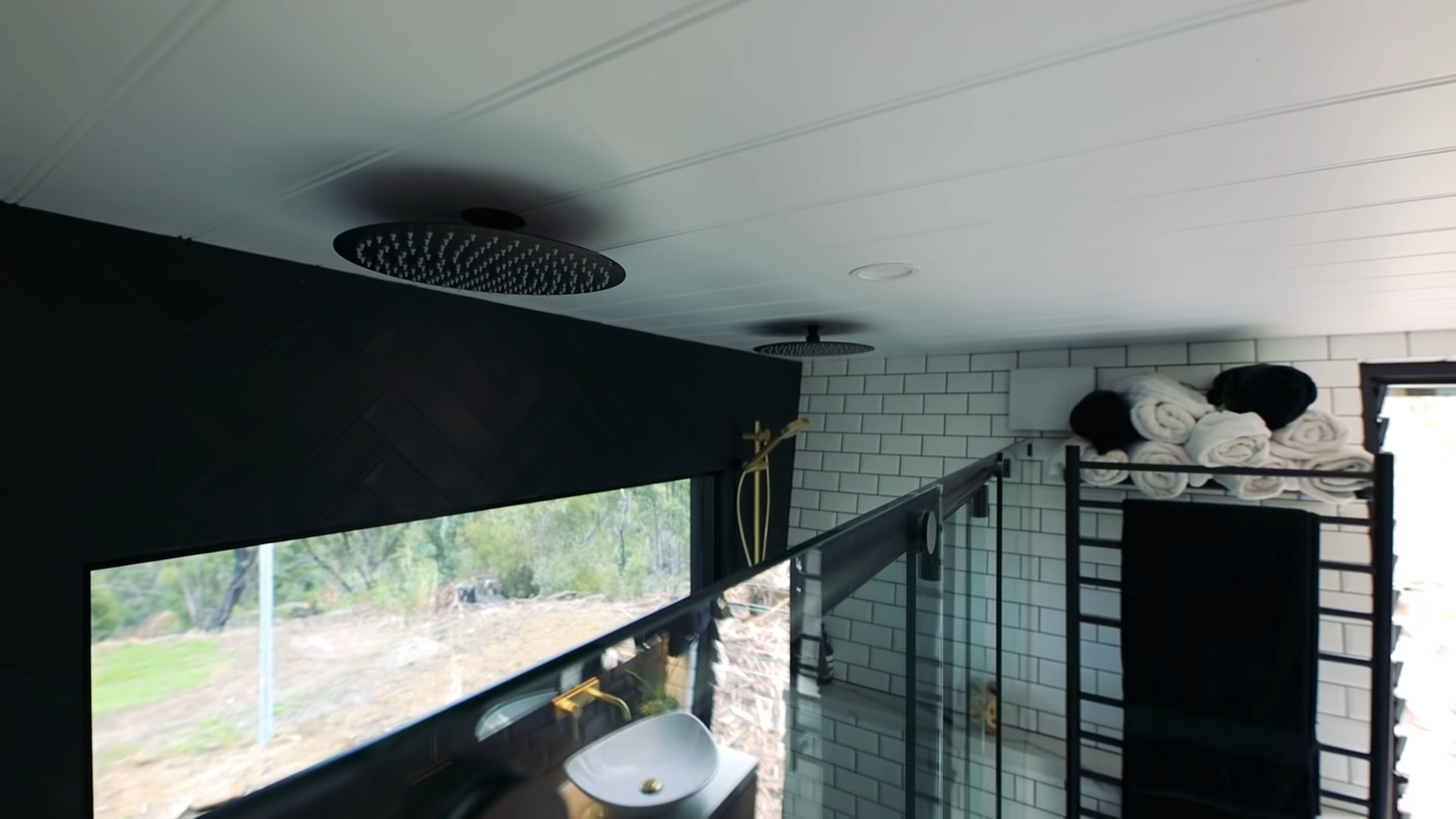 This Tiny House's full bathroom has a shower big enough for two which includes dual rain shower heads and a paneled ceiling.