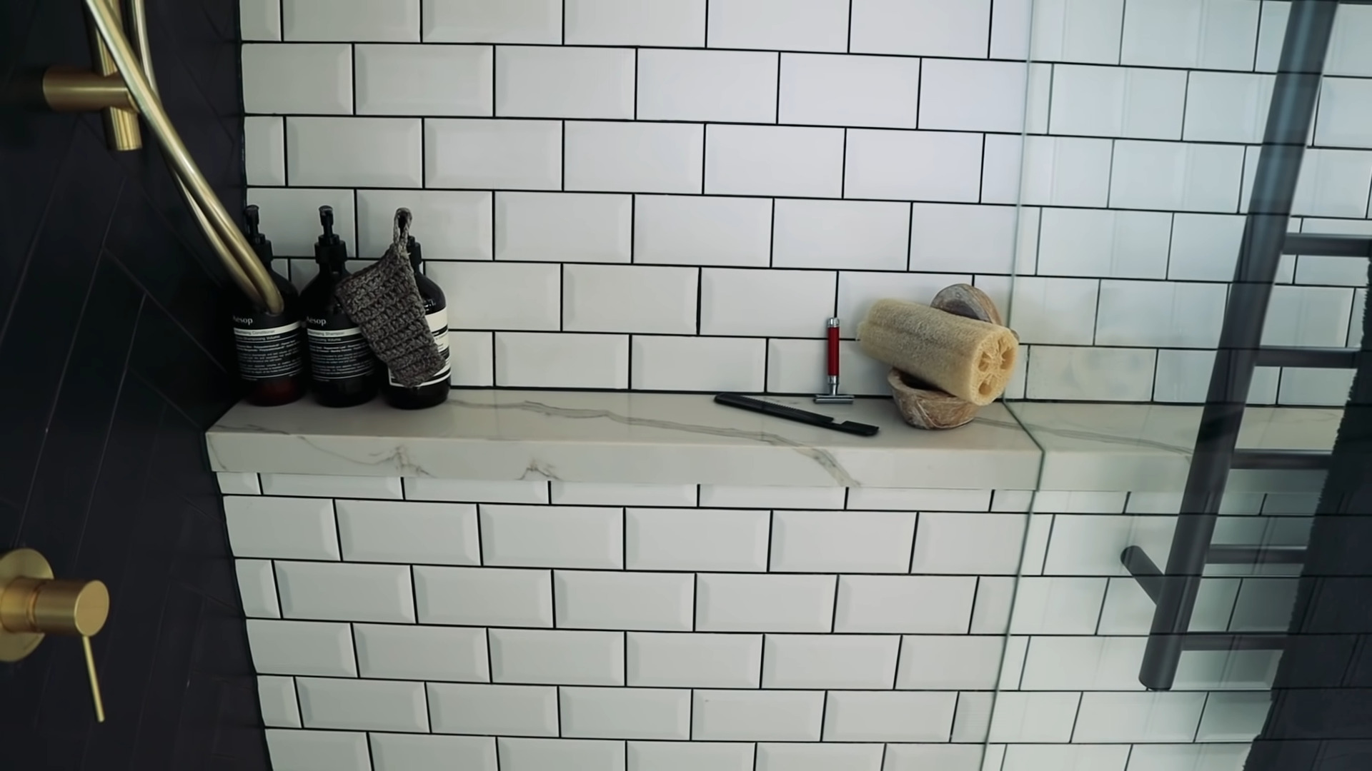 Closeup view of the marble shower shelf. do tiny houses have bathrooms