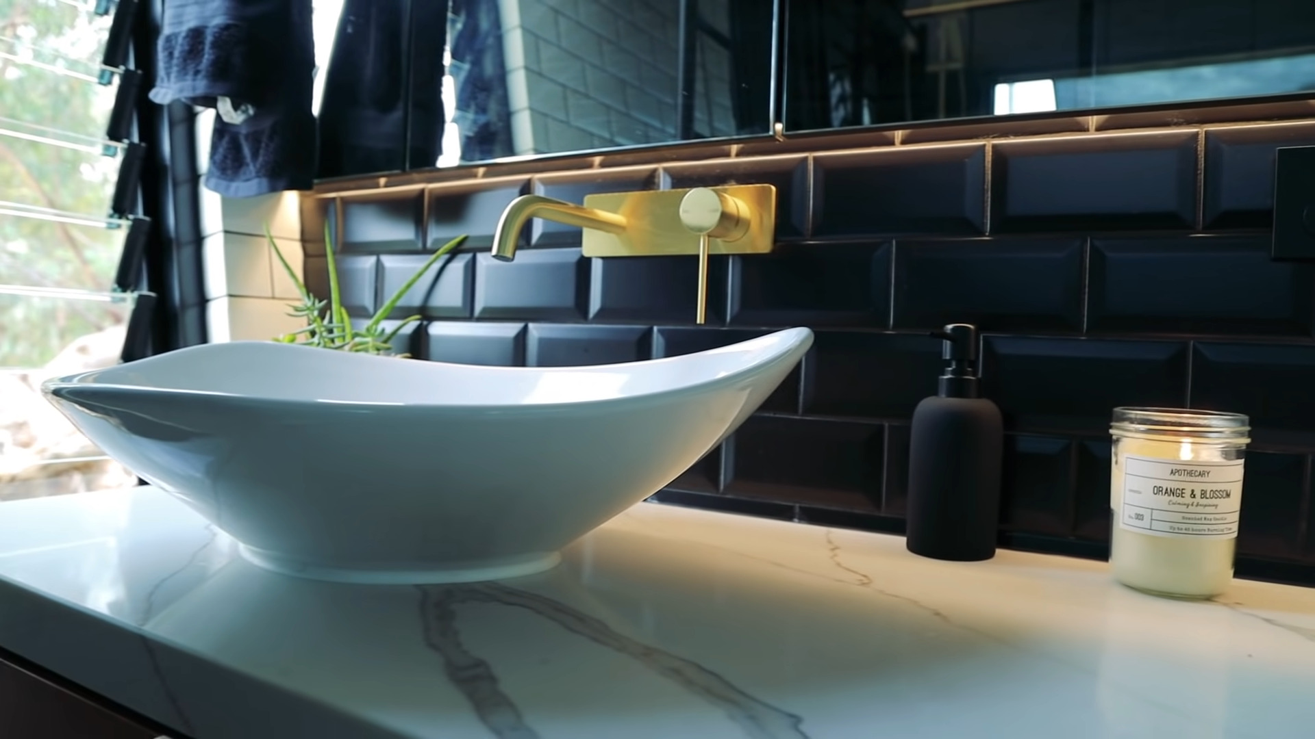 closeup view of the bowl sink, marble countertops and dark subway tile backsplash with gold fixtures