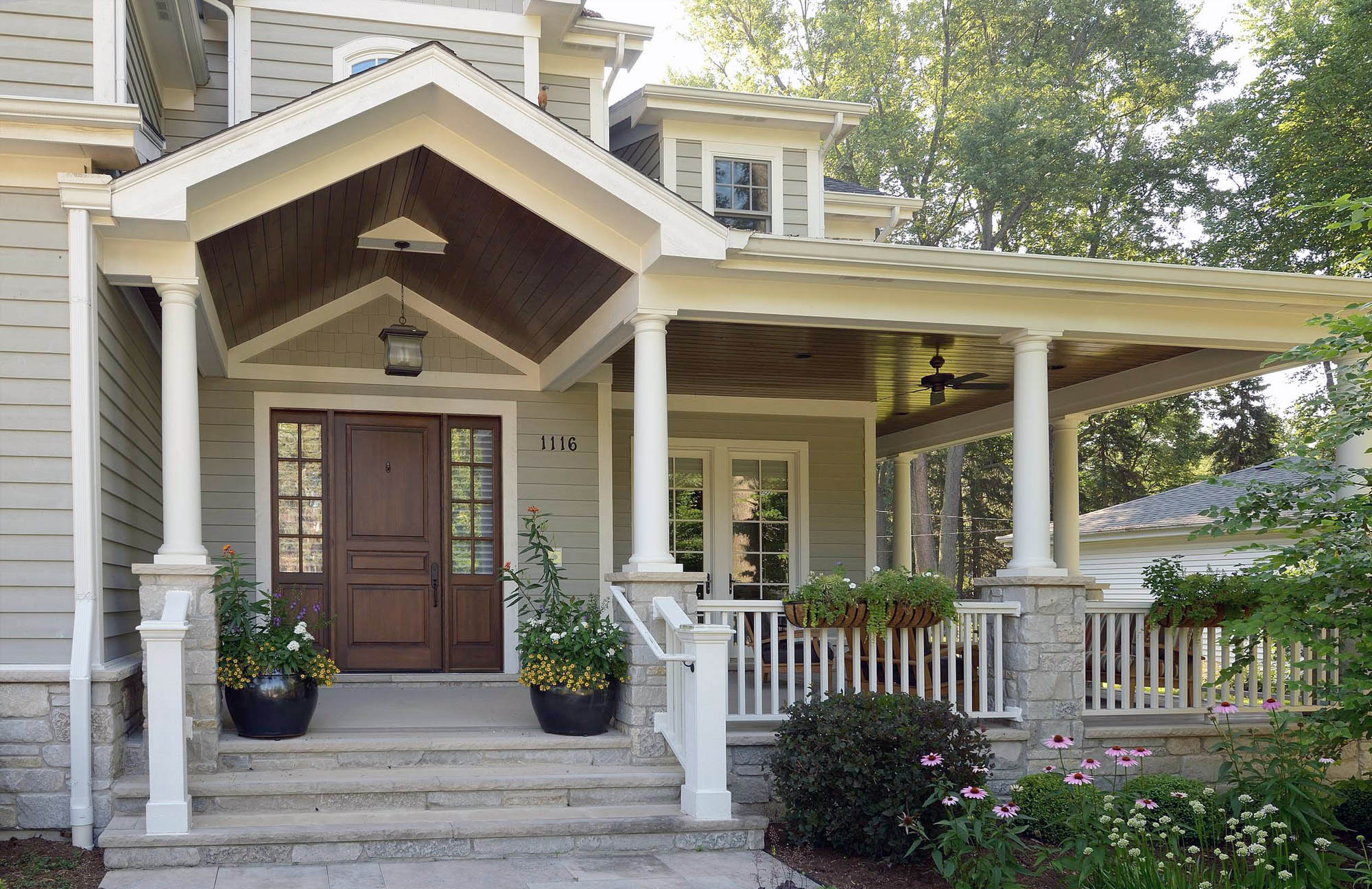 Beautiful custom home with pale green gray siding and real wood stained front door.