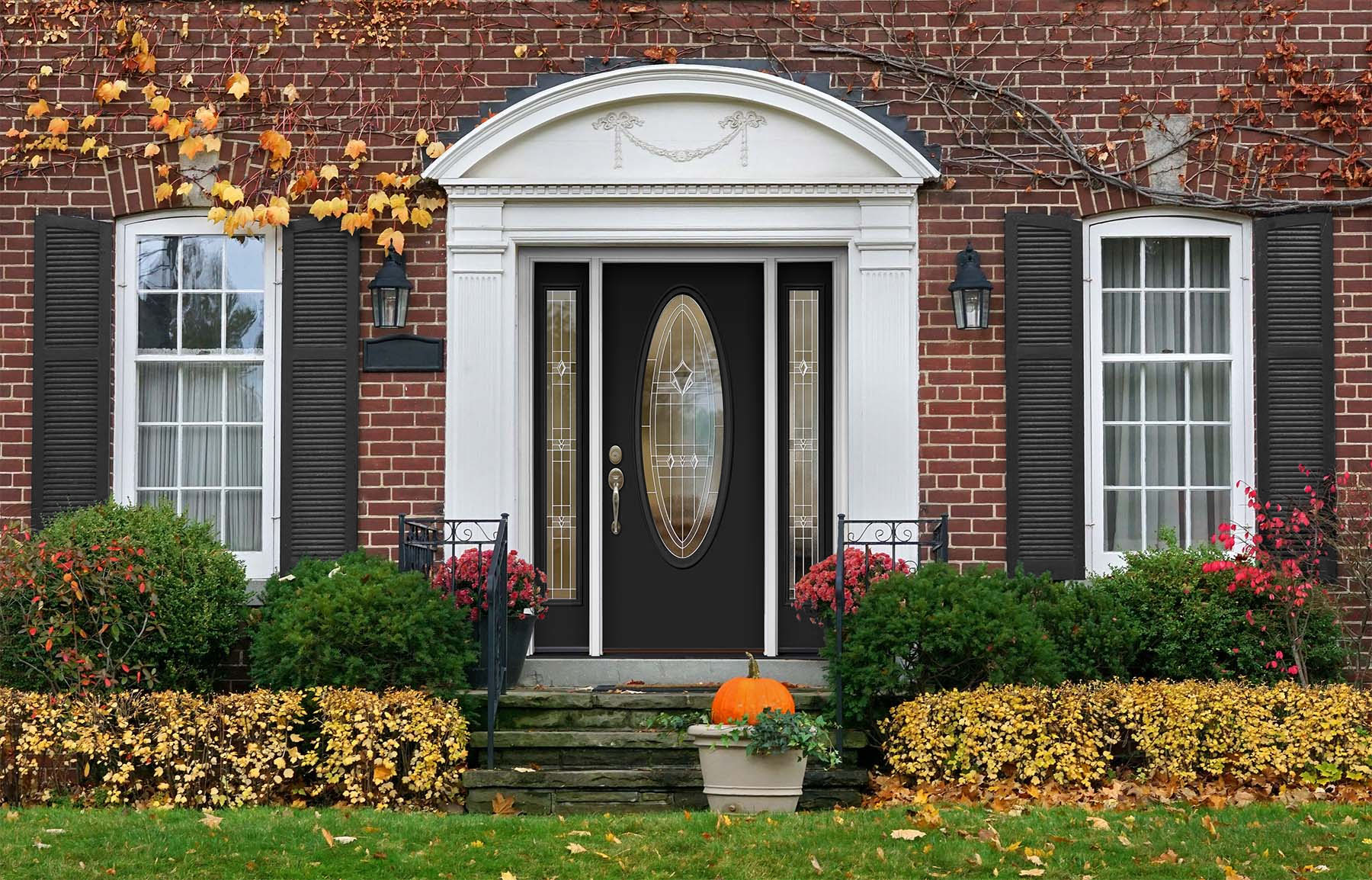 Red brick home with charcoal gray shutters and matching front door.