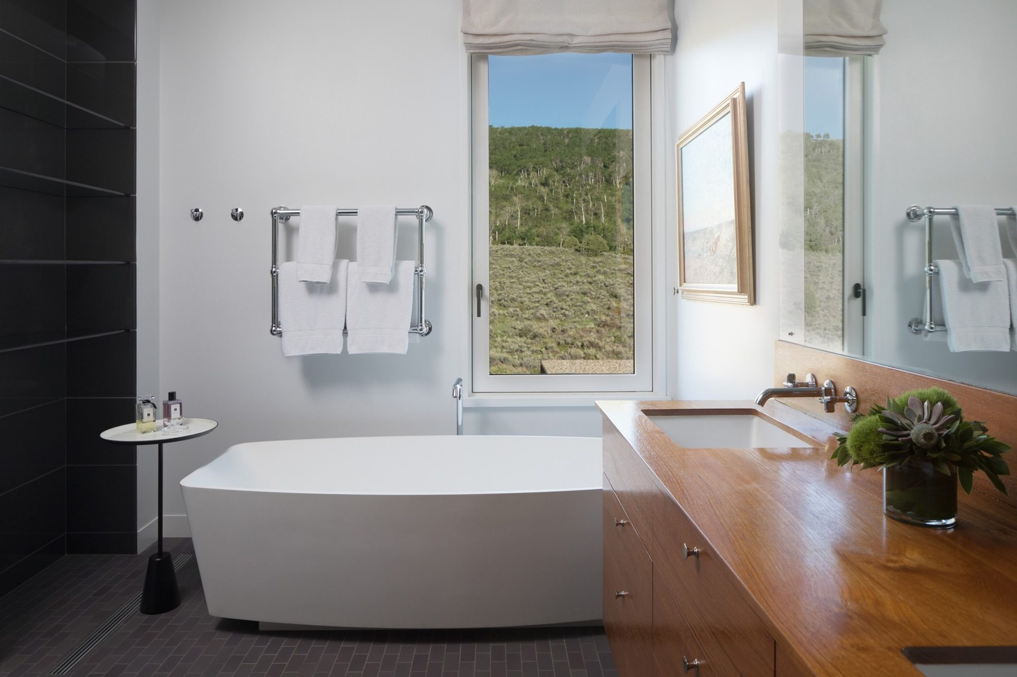 Modern bathroom design with an all wood vanity including a wood countertop and backsplash. Contemporary soaking tub and granite gray tiles.