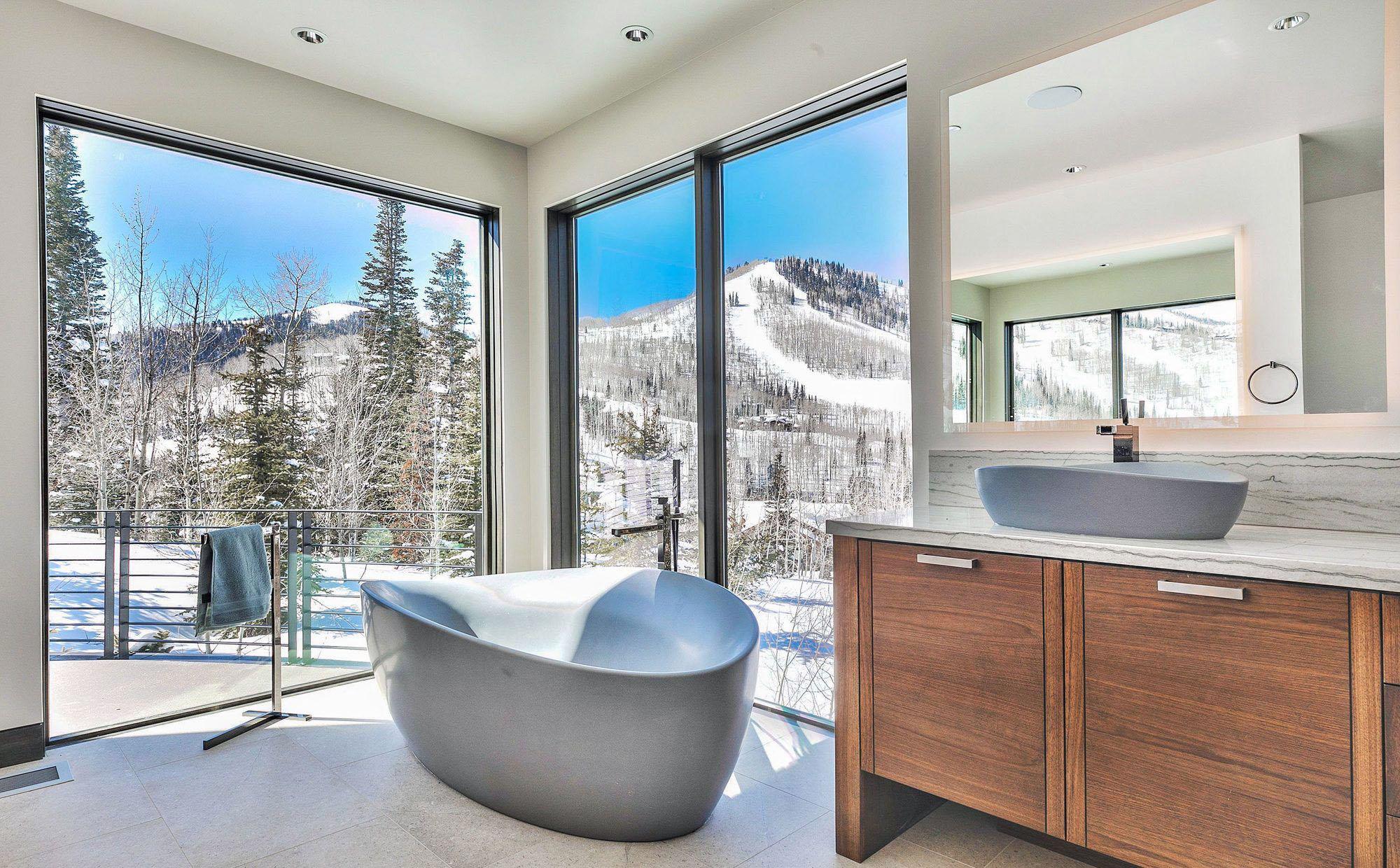 Modern bathroom featuring gray soaking tub, wood vanity with marble countertop. Huge walls of glass.