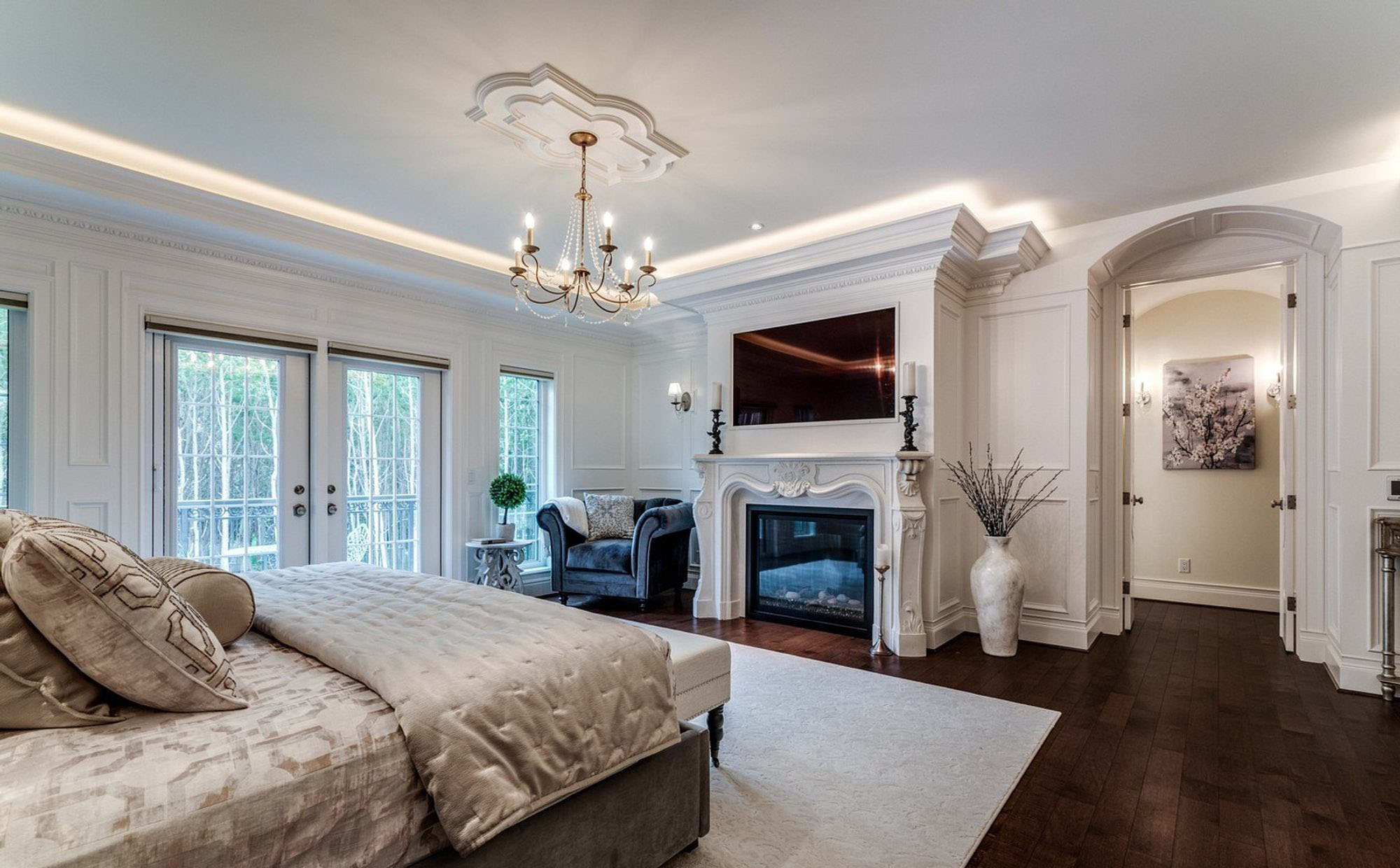 Master bedroom with built in gas fireplace and wall paneling surround.