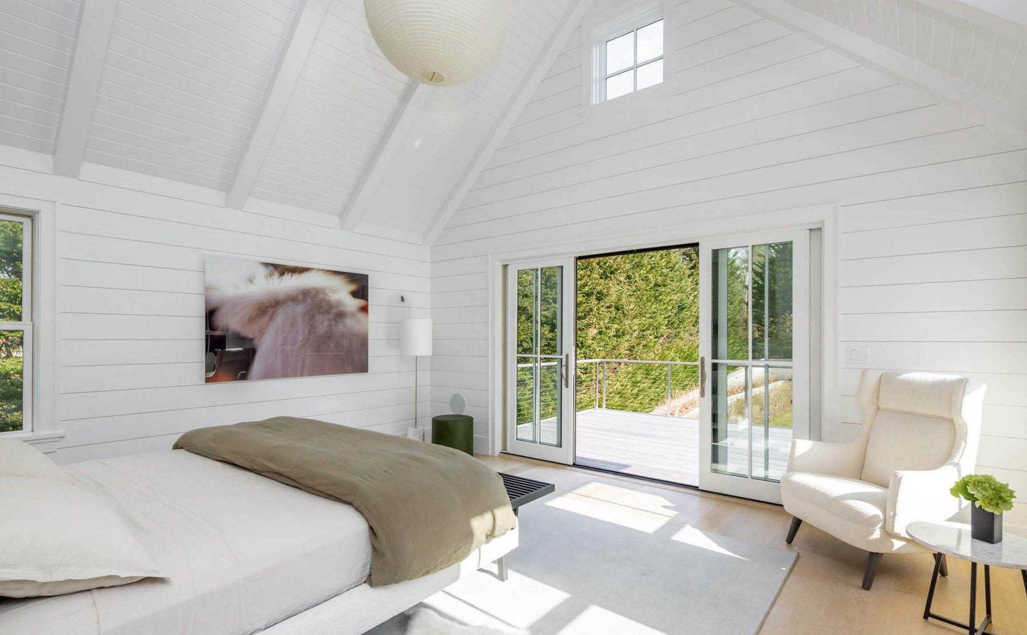 Master bedroom with vaulted ceilings and exposed beams. Horizontal shiplap wall paneling painted all white.