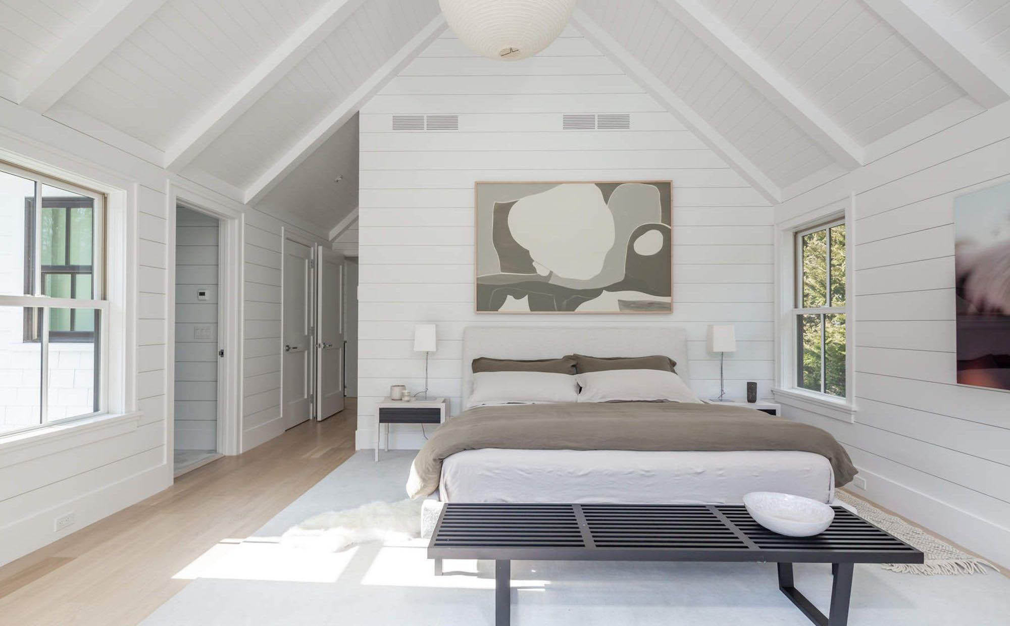 White shiplap walls with vaulted ceilings and exposed beams.