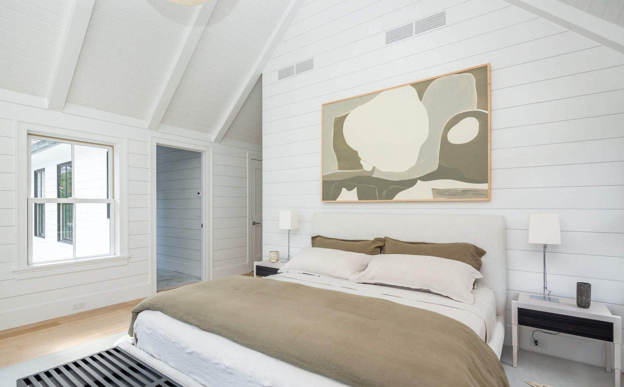 Bedroom shiplap painted white with vaulted ceilings and exposed beams.