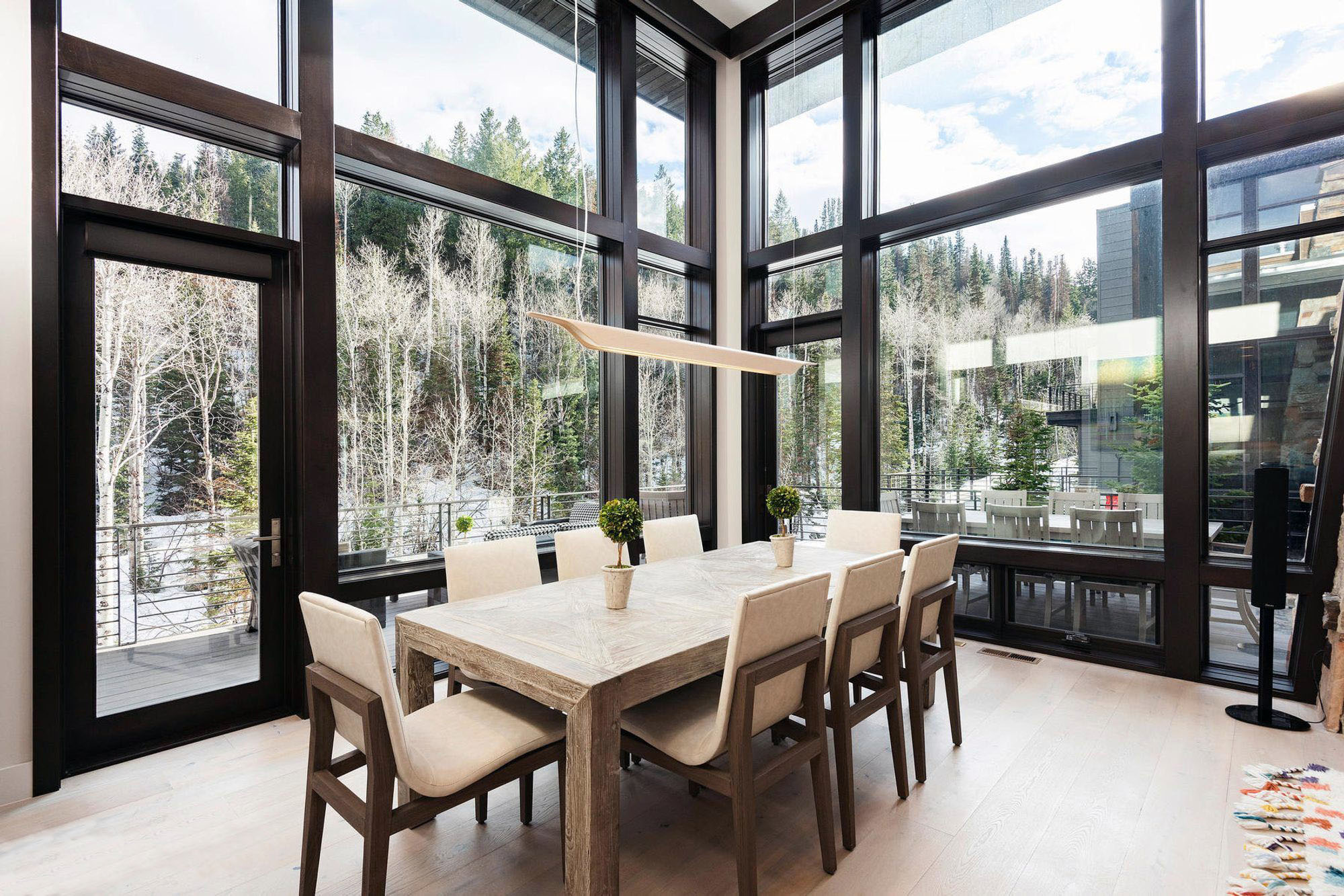 Modern dining room with floor to ceiling glass walls.