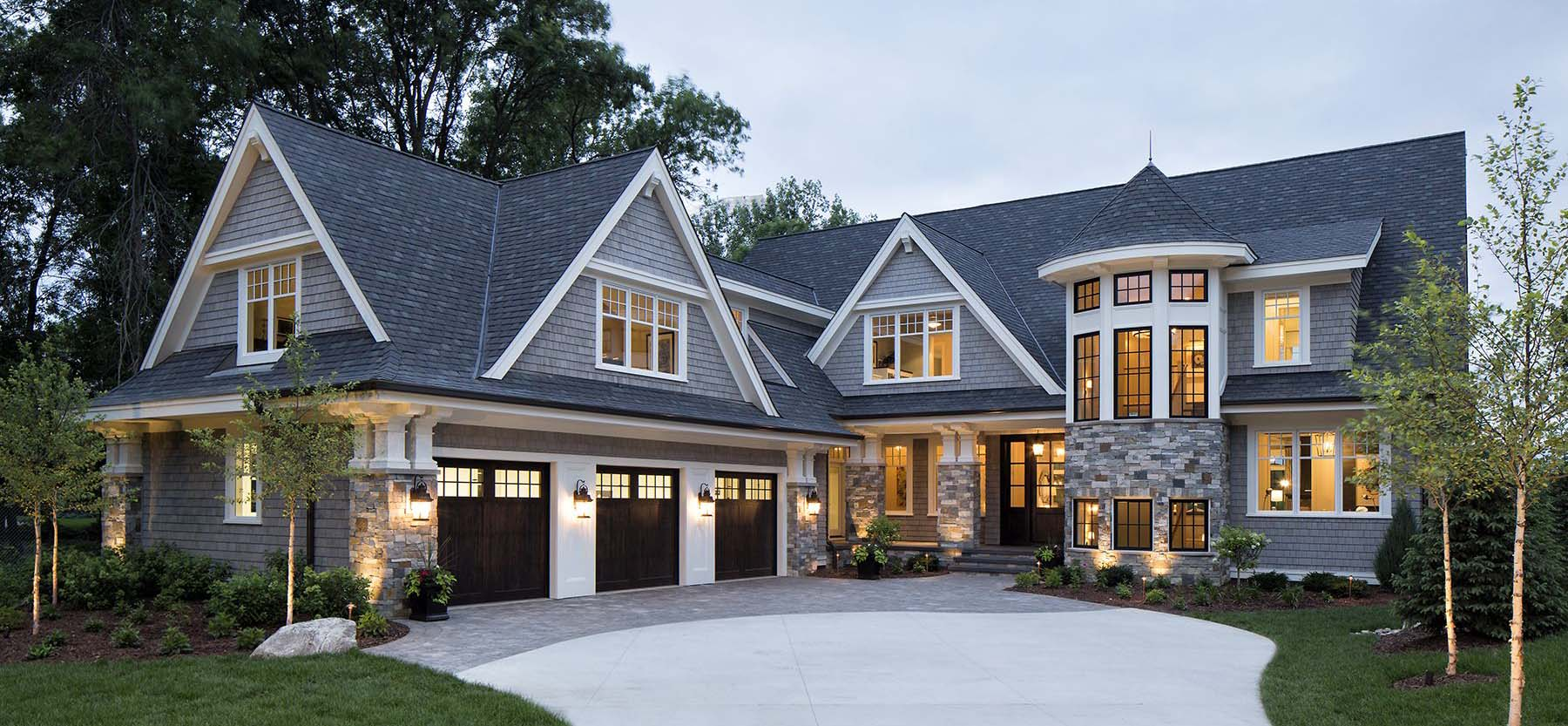 Beautiful custom home with blue gray siding and espresso stained real wood front door.