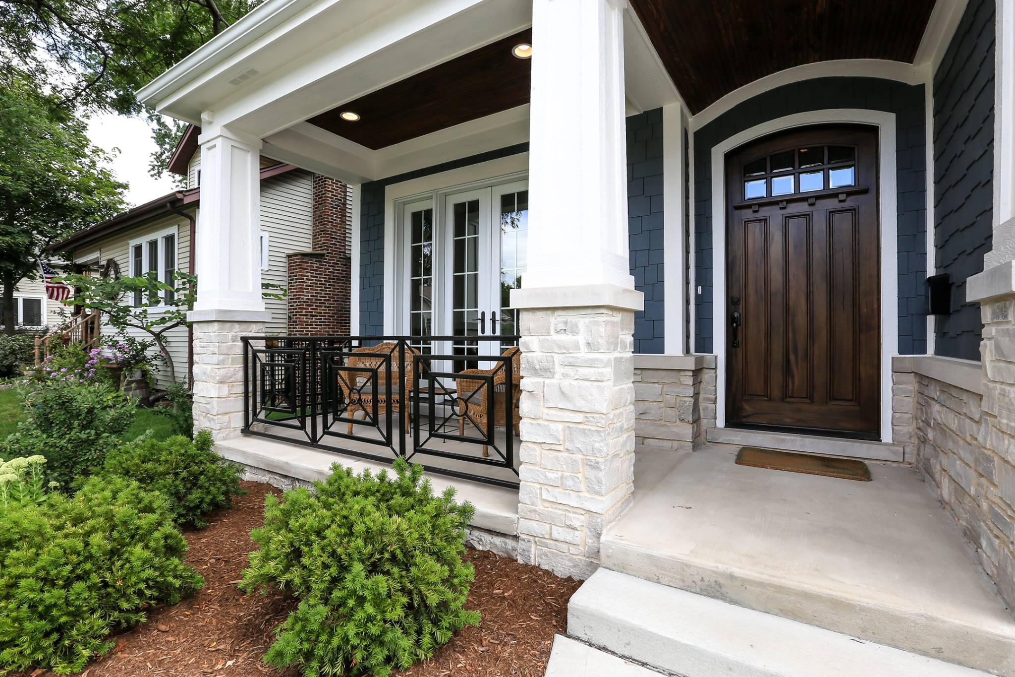 Dark blue siding with dark brown stained front door, white trim and light colored stone veneer.