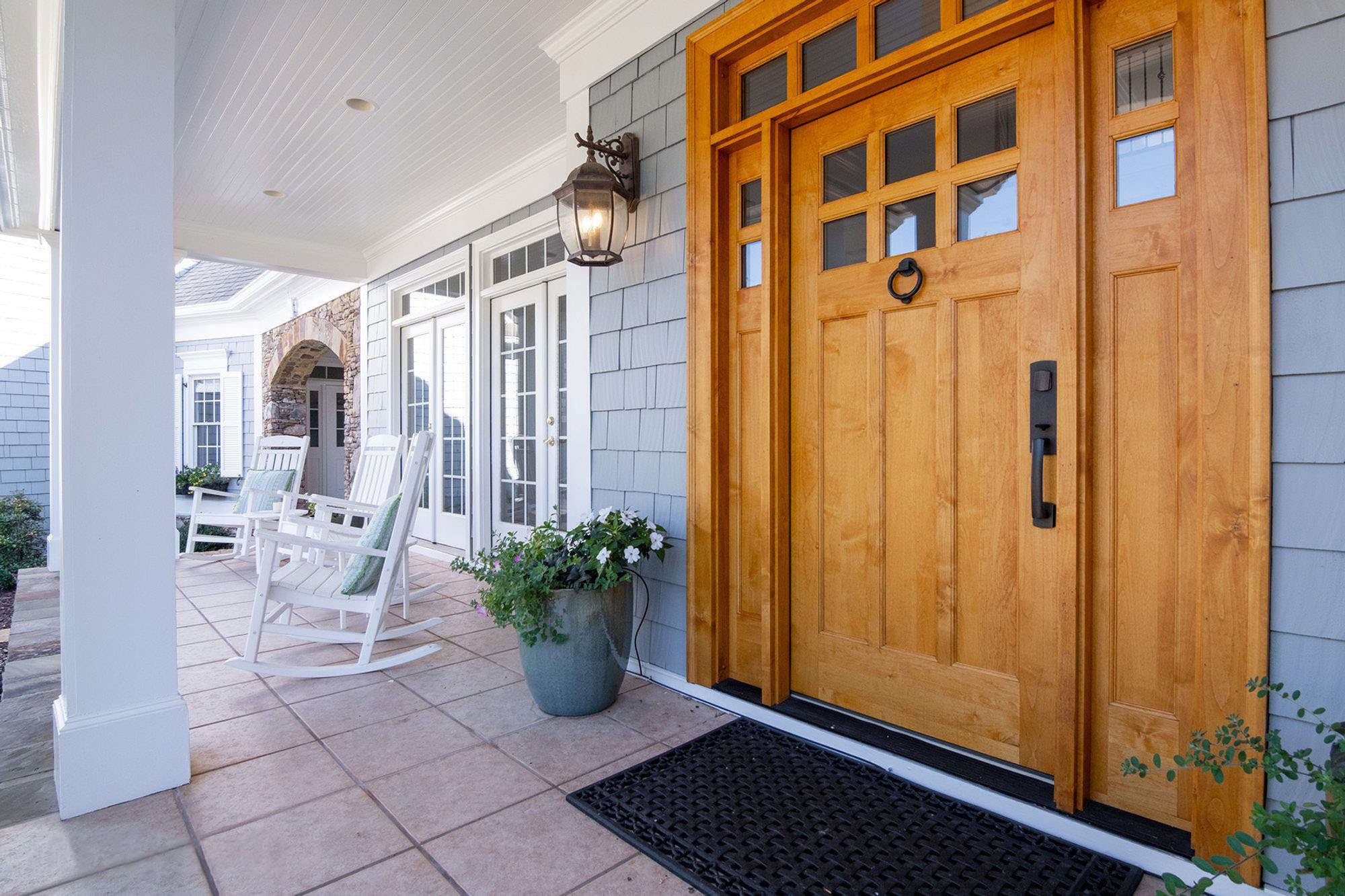 Light blue cedar shake siding with a natural wood front door. Side and top glass transoms with black door hardware.