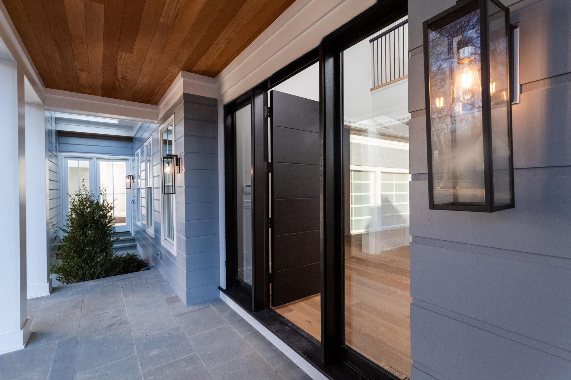 Modern black front door on a custom home with blue lap siding, a covered front porch and wood panel ceiling.
