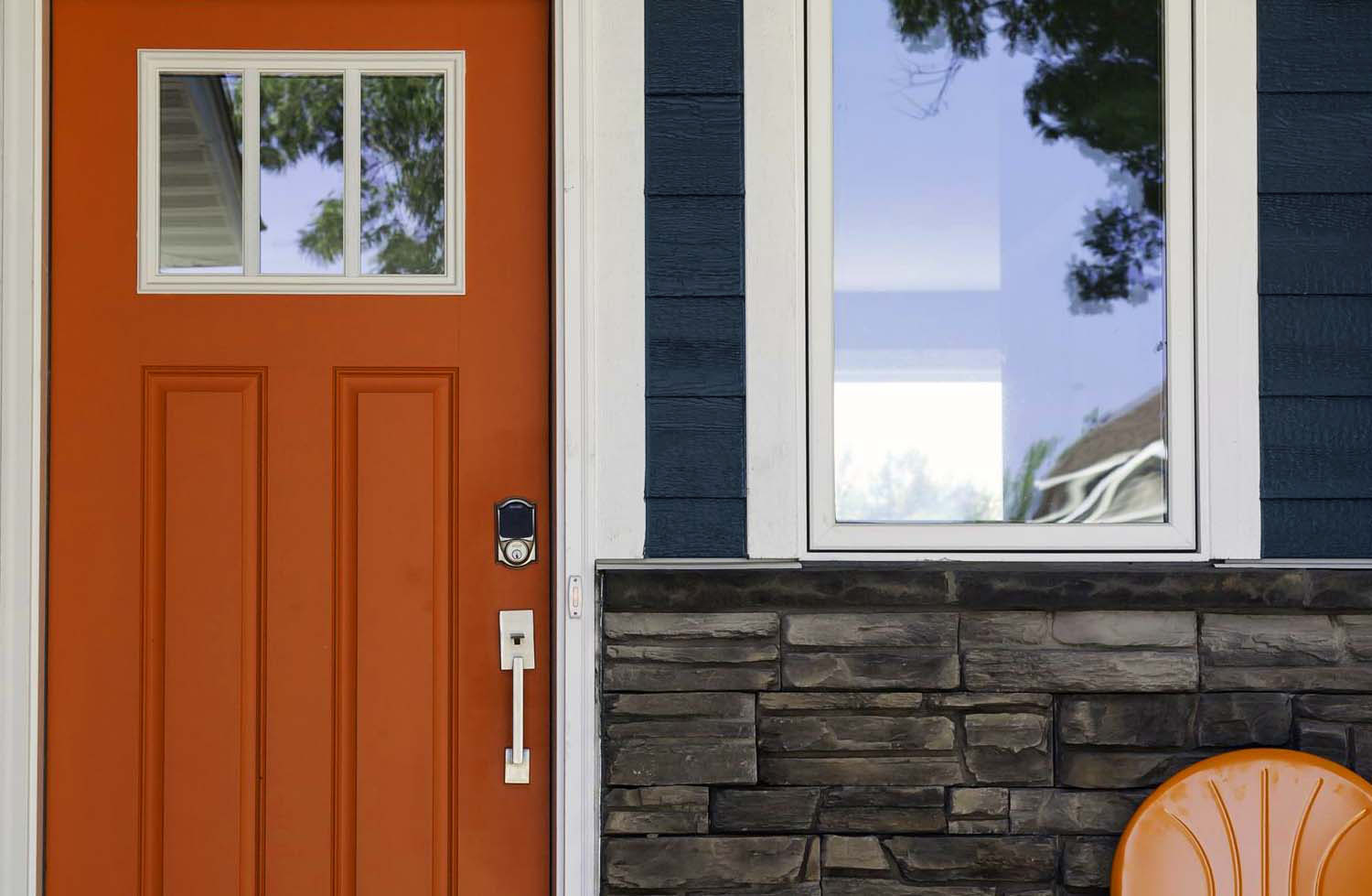 Dark blue house with a bright reddish orange front door and real stone veneer.