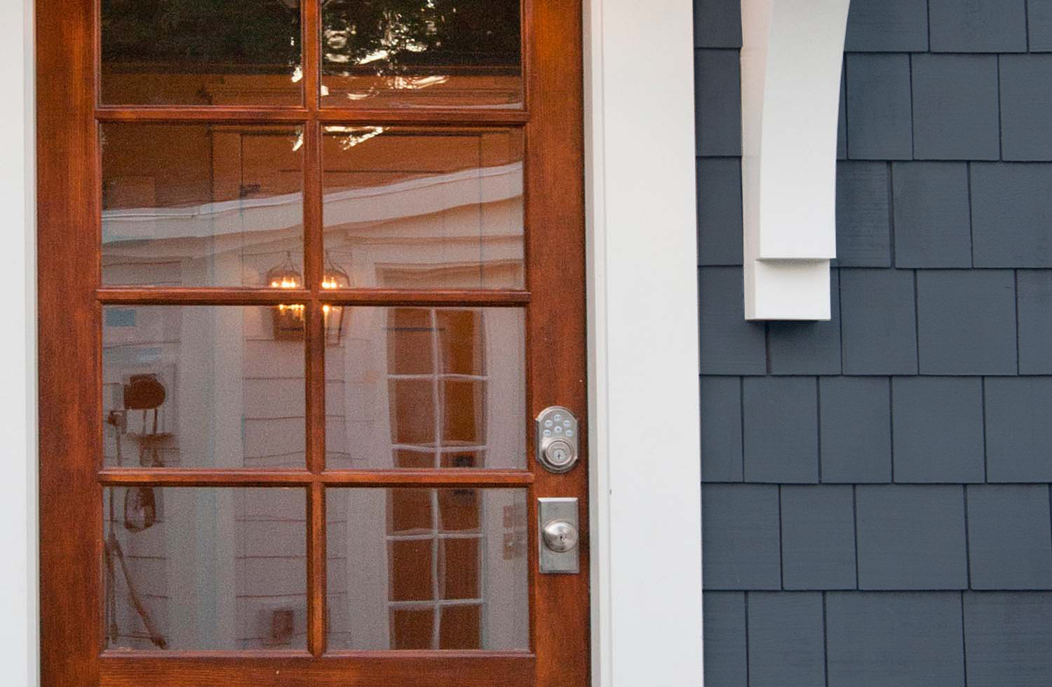 Navy blue cedar shake siding with white trim and a real wood front door.