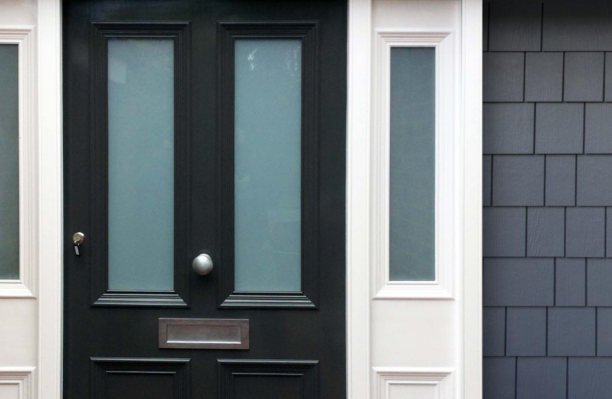 English style black front door with medium blue cedar shake siding. White trim with glass side lights.