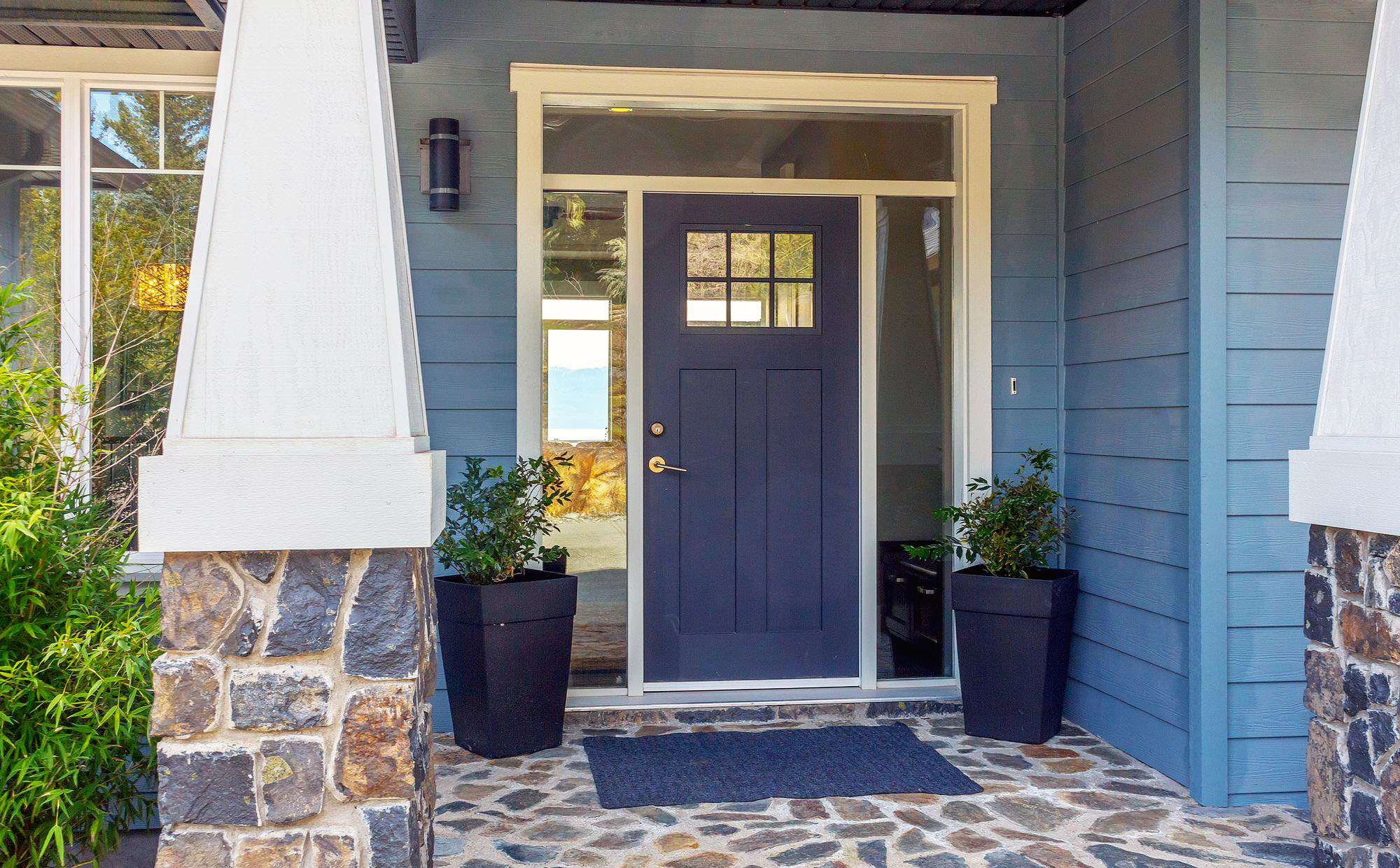 This beautiful blue home features light blue siding, a deep blue front door and real stones with a blueish coloring.