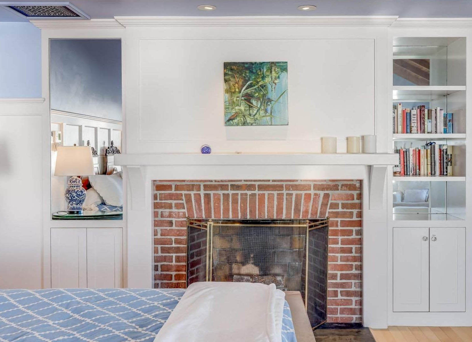 Red brick wood burning bedroom fireplace with wood surround and built ins.