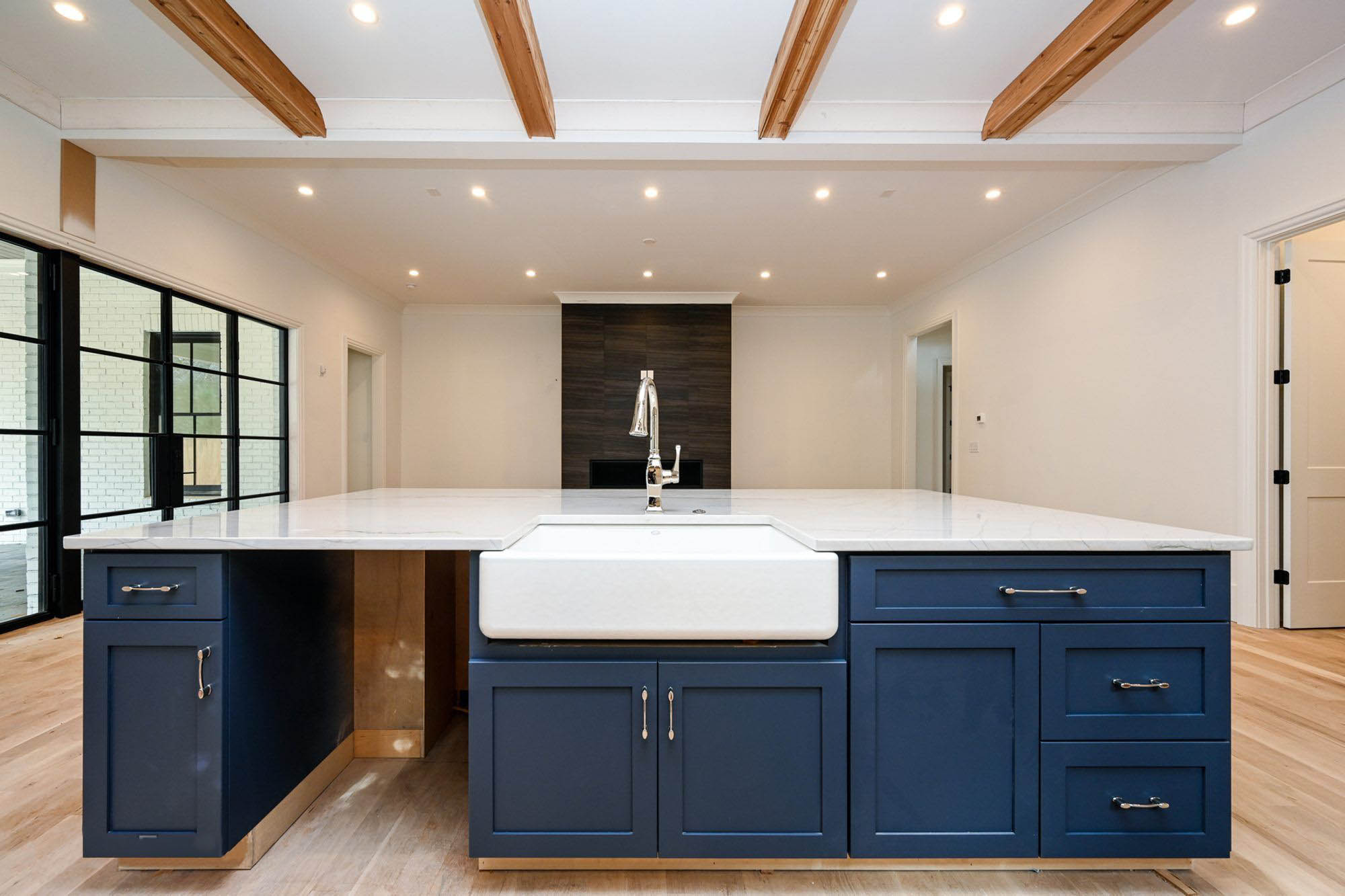 blue shaker style island cabinets with marble counters and white enamel undermount farmhouse sink