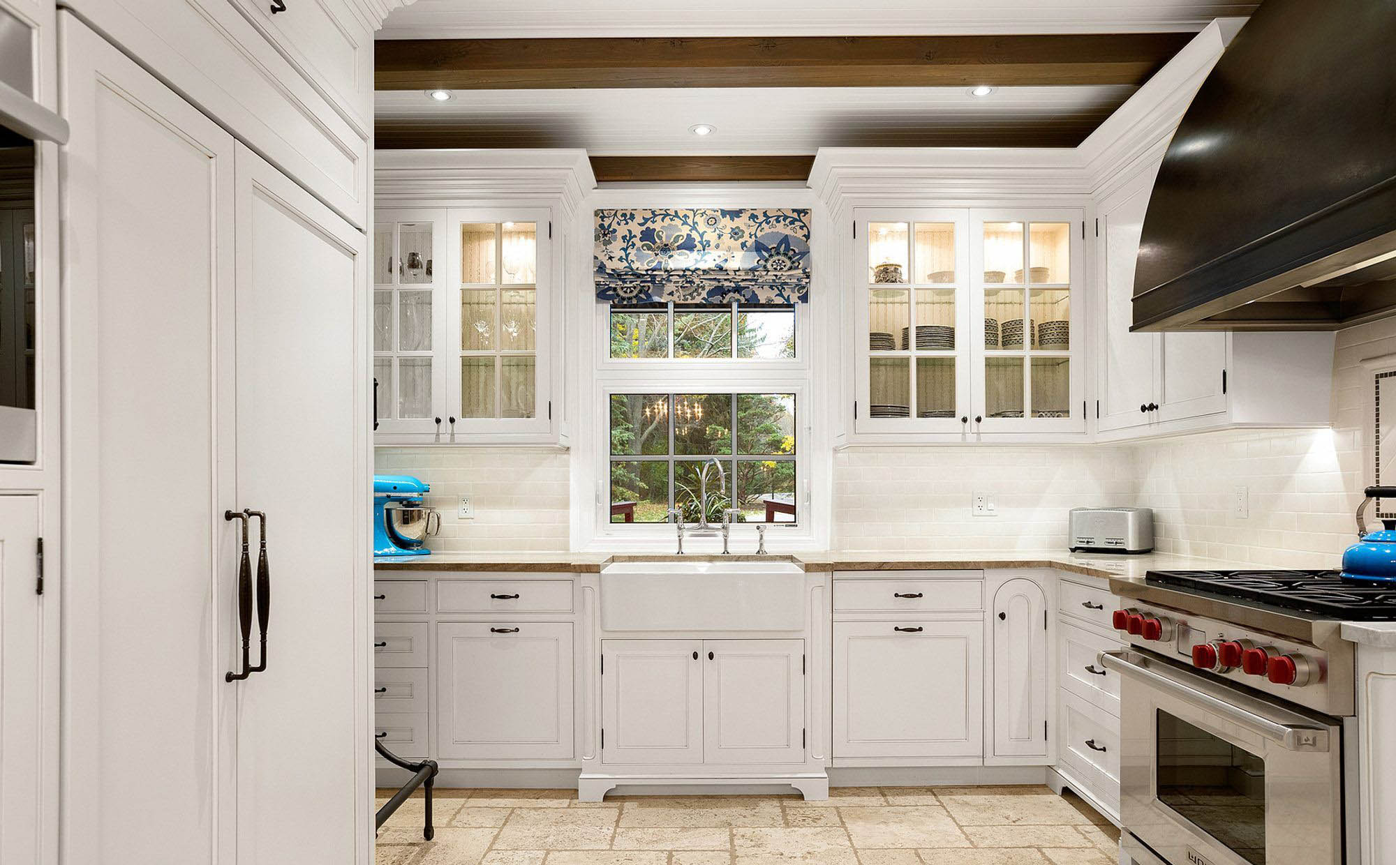 country style kitchen with a white farmhouse sink and white cabinets, exposed wood ceiling beams, stainless wolf appliances, built in refrigerator