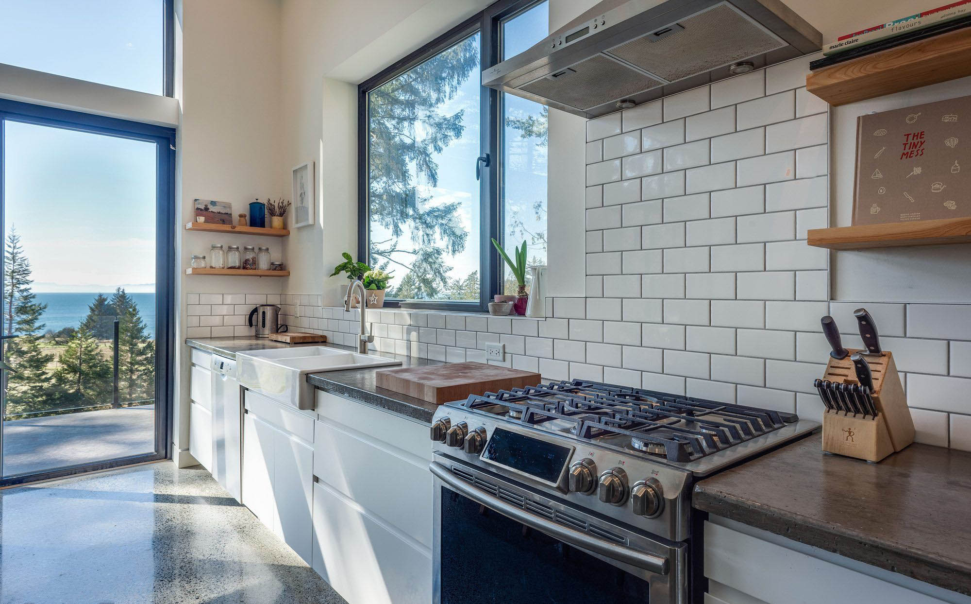 charming country style kitchen with a white enamel farmhouse sink and stainless appliances with white subway tile backsplash