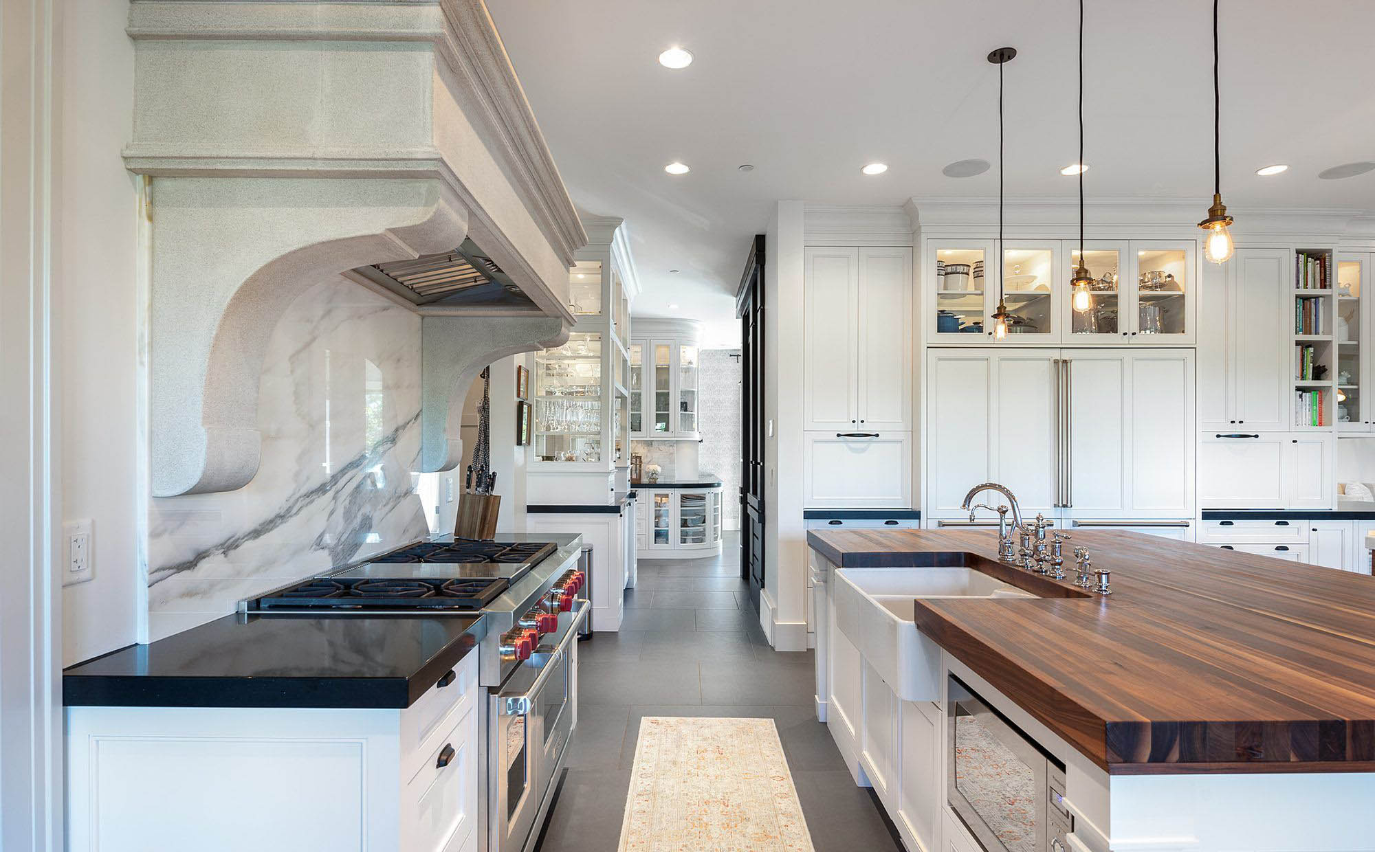 luxury kitchen design with a solid slab backsplash, butcher block countertops white farmhouse sink, and built in refrigerator.
