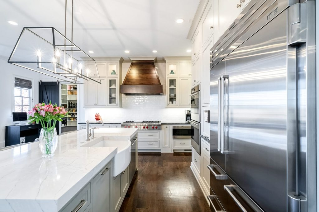 beautiful kitchen with an exposed apron white farmhouse sink and marble quartz countertops