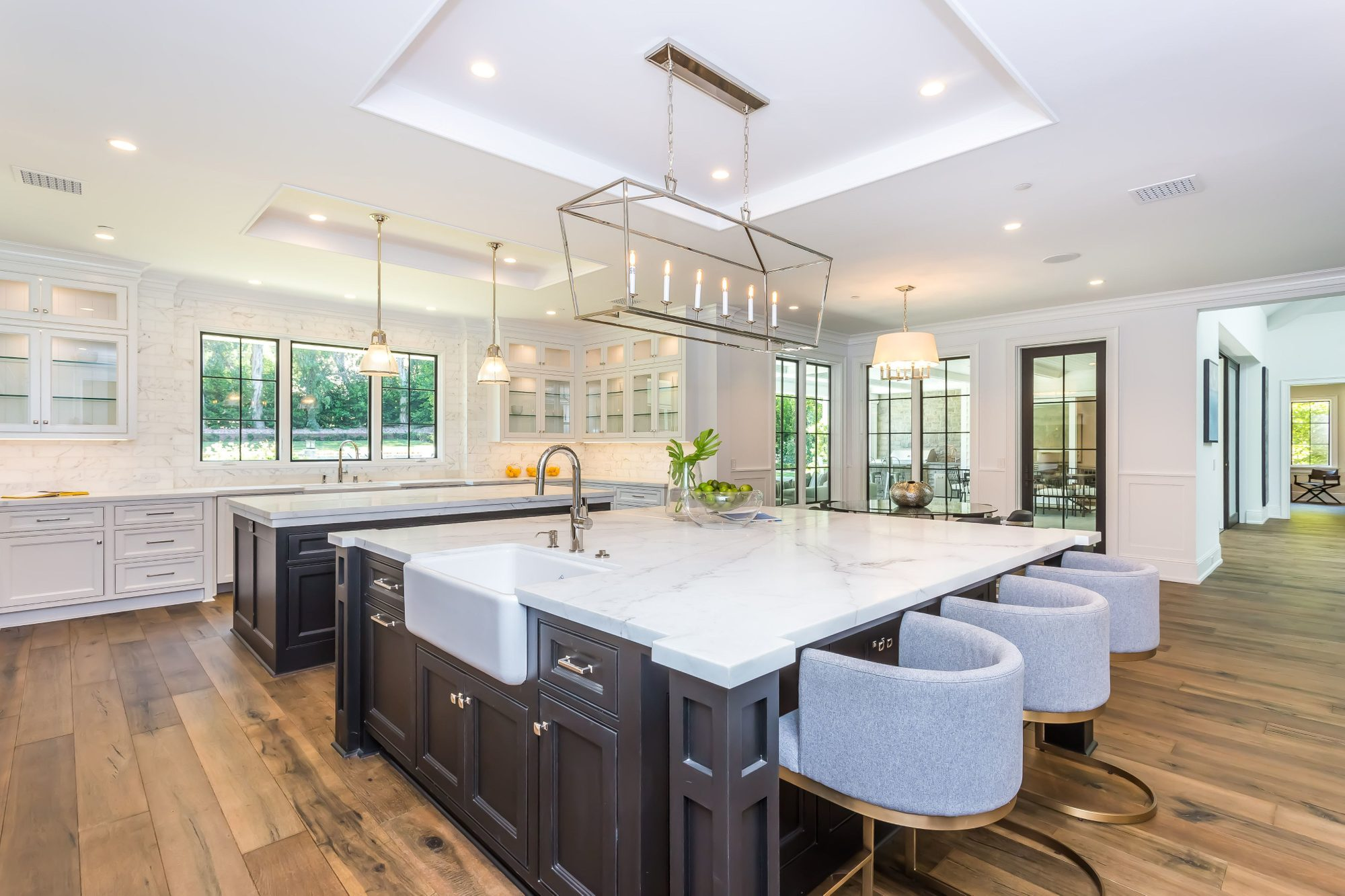Huge kitchen with two white enamel farmhouse sinks, white cabinets and 2 dark brown center islands