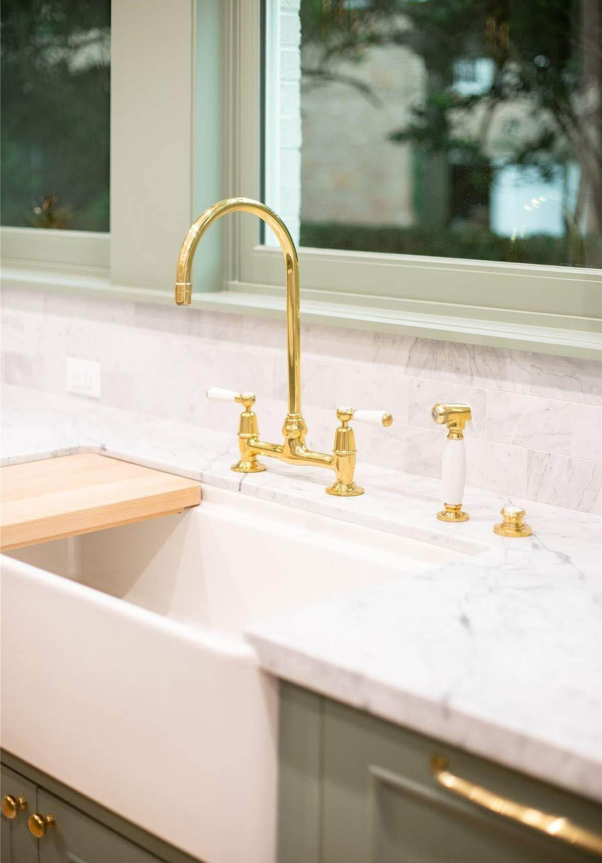 closeup view of a white enamel farmhouse kitchen sink with gold faucet and green cabinets